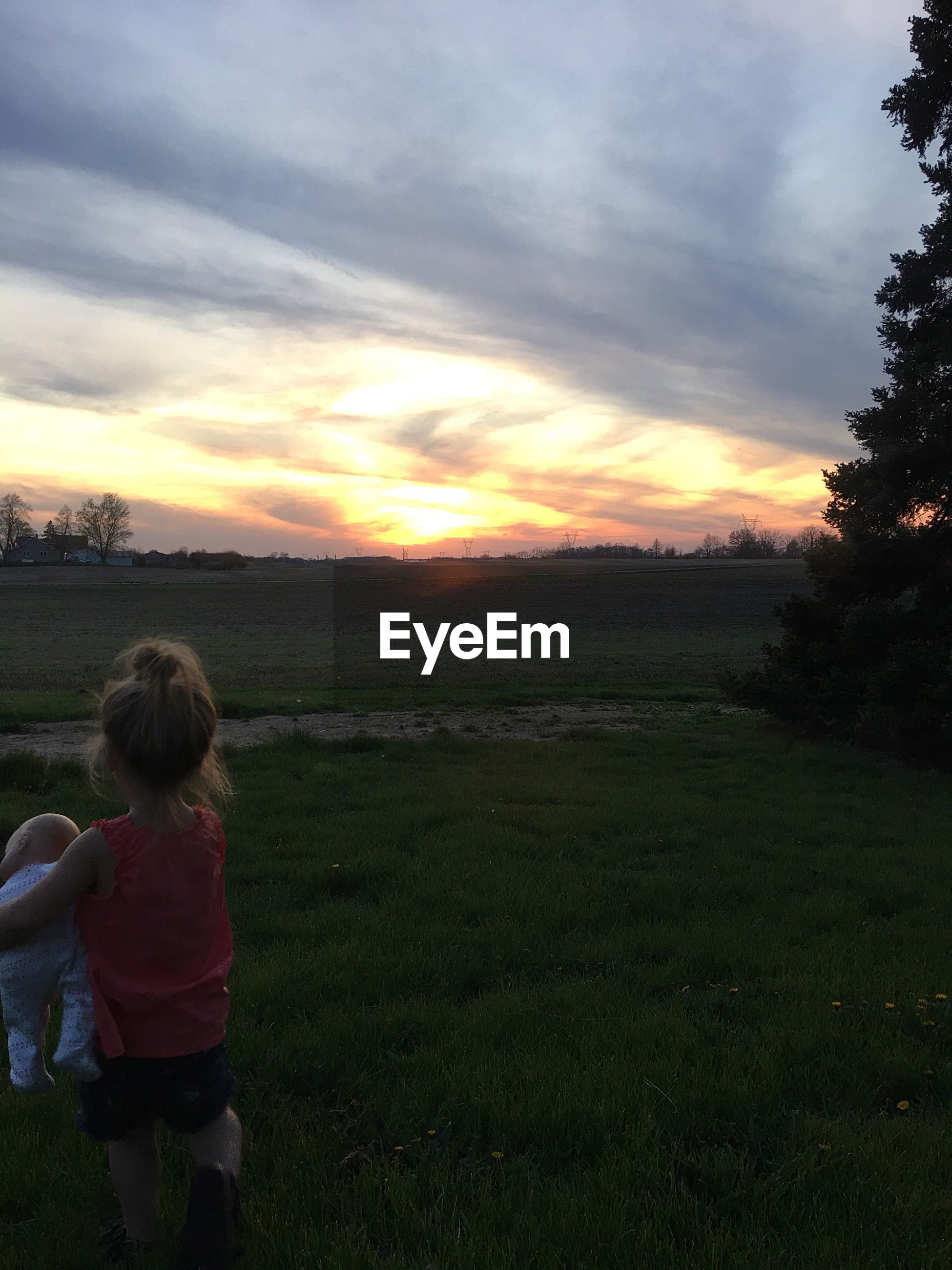 childhood, sunset, leisure activity, rear view, lifestyles, elementary age, standing, girls, boys, tree, field, casual clothing, scenics, sky, tranquility, beauty in nature, cloud - sky, tranquil scene, person, innocence, rural scene, outdoors, children only, atmospheric mood, orange color, cultivated land, sunbeam