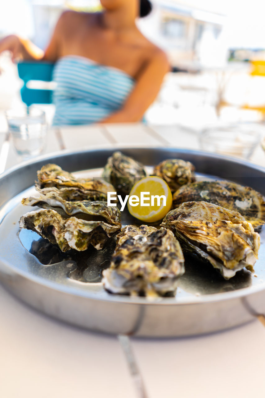 food, food and drink, plate, healthy eating, table, ready-to-eat, seafood, freshness, wellbeing, indoors, serving size, one person, oyster, focus on foreground, selective focus, close-up, citrus fruit, lemon, fruit