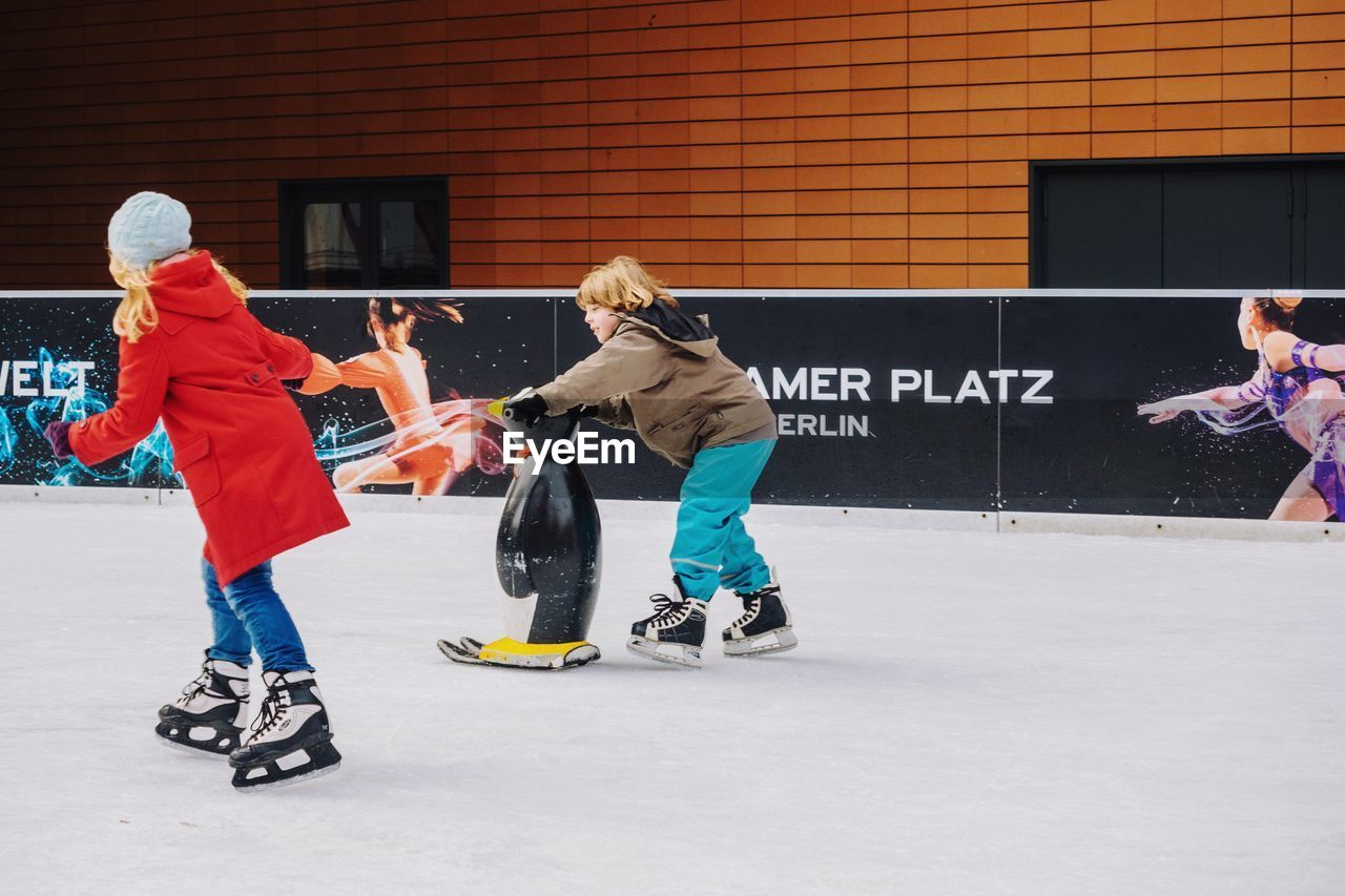 real people, playing, lifestyles, fun, leisure activity, full length, men, day, togetherness, building exterior, outdoors, ice rink, people