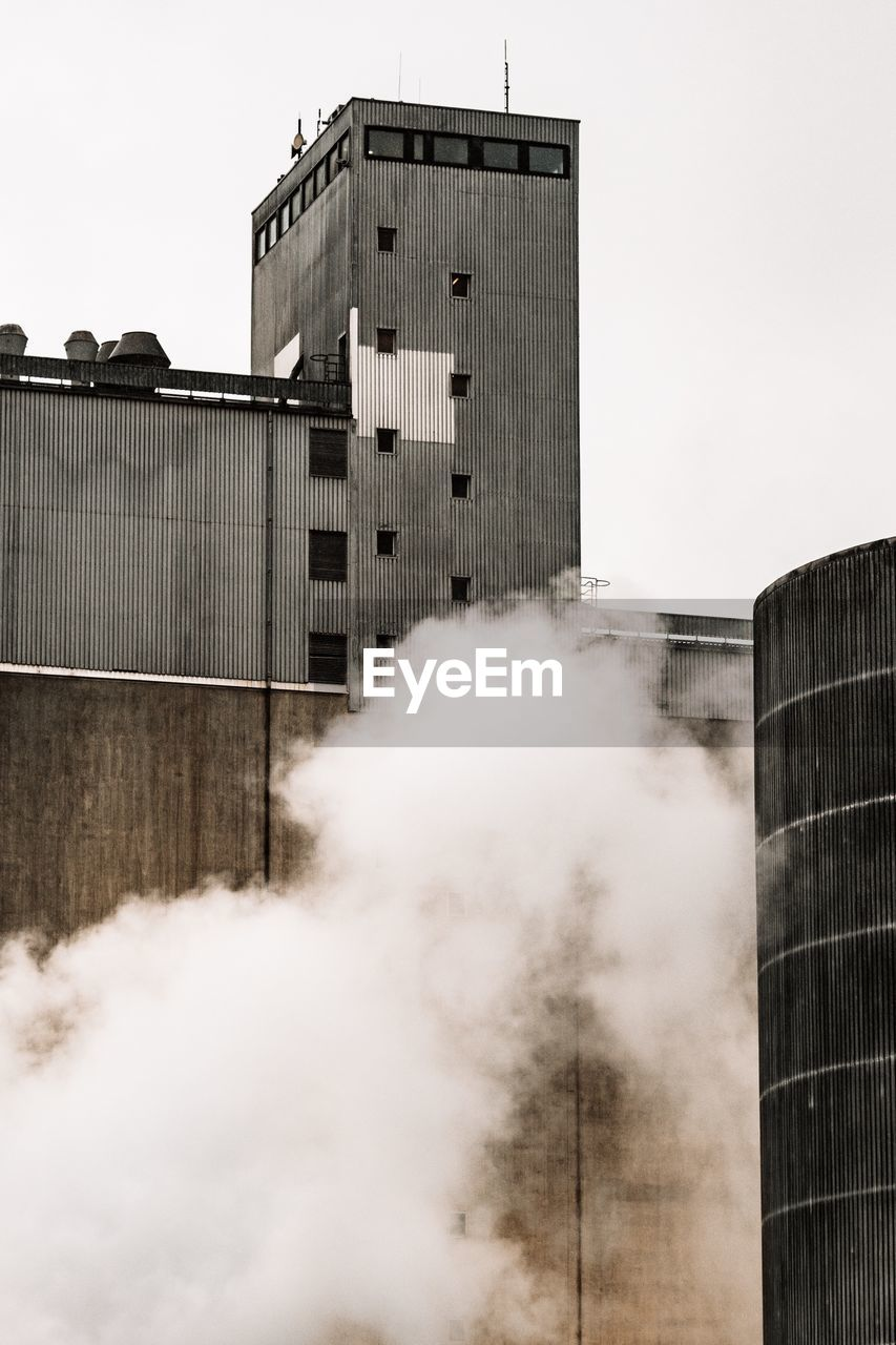 building exterior, architecture, built structure, sky, smoke - physical structure, pollution, building, industry, factory, nature, clear sky, day, outdoors, no people, city, environmental issues, air pollution, smoke stack, environment, modern