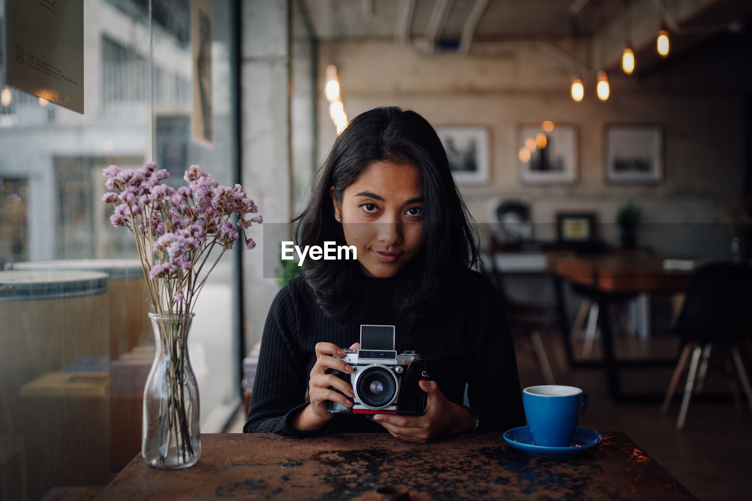 Portrait of woman photographing with camera at table in cafe