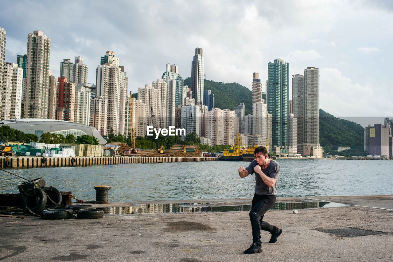 FULL LENGTH OF MAN STANDING BY MODERN BUILDINGS IN CITY