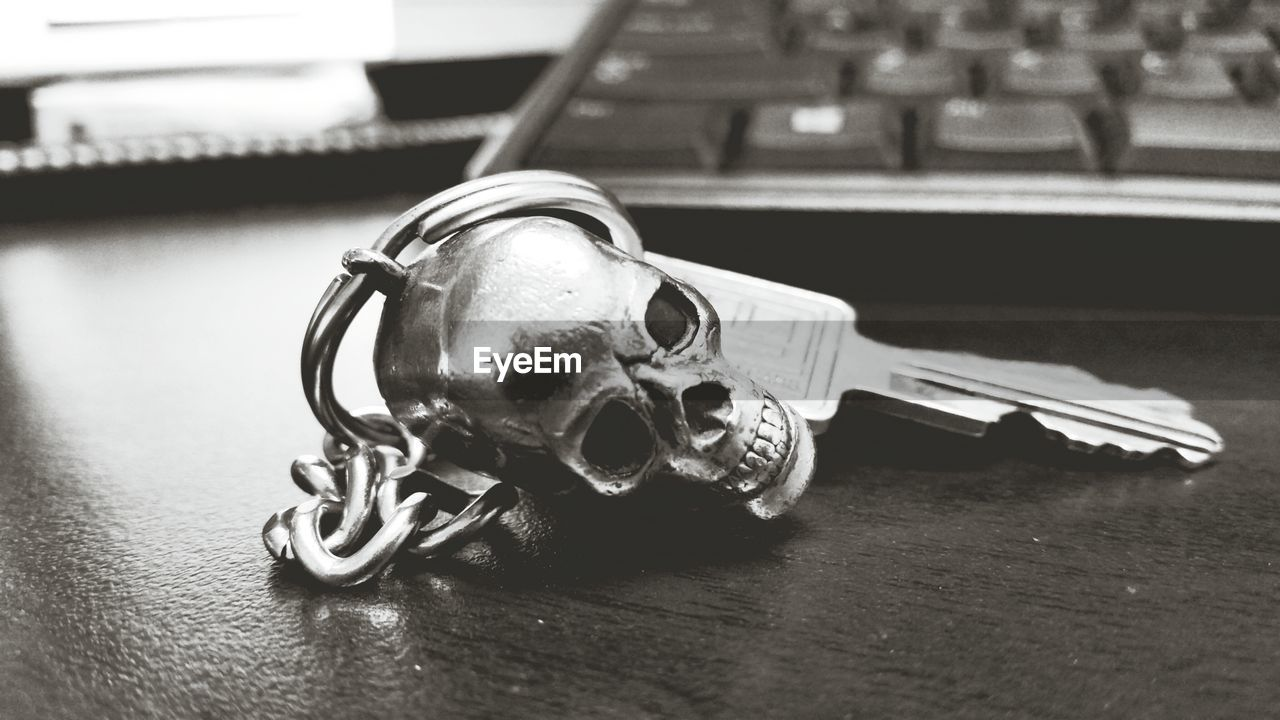 Close-up Of Artificial Human Skull On Ring Key At Table