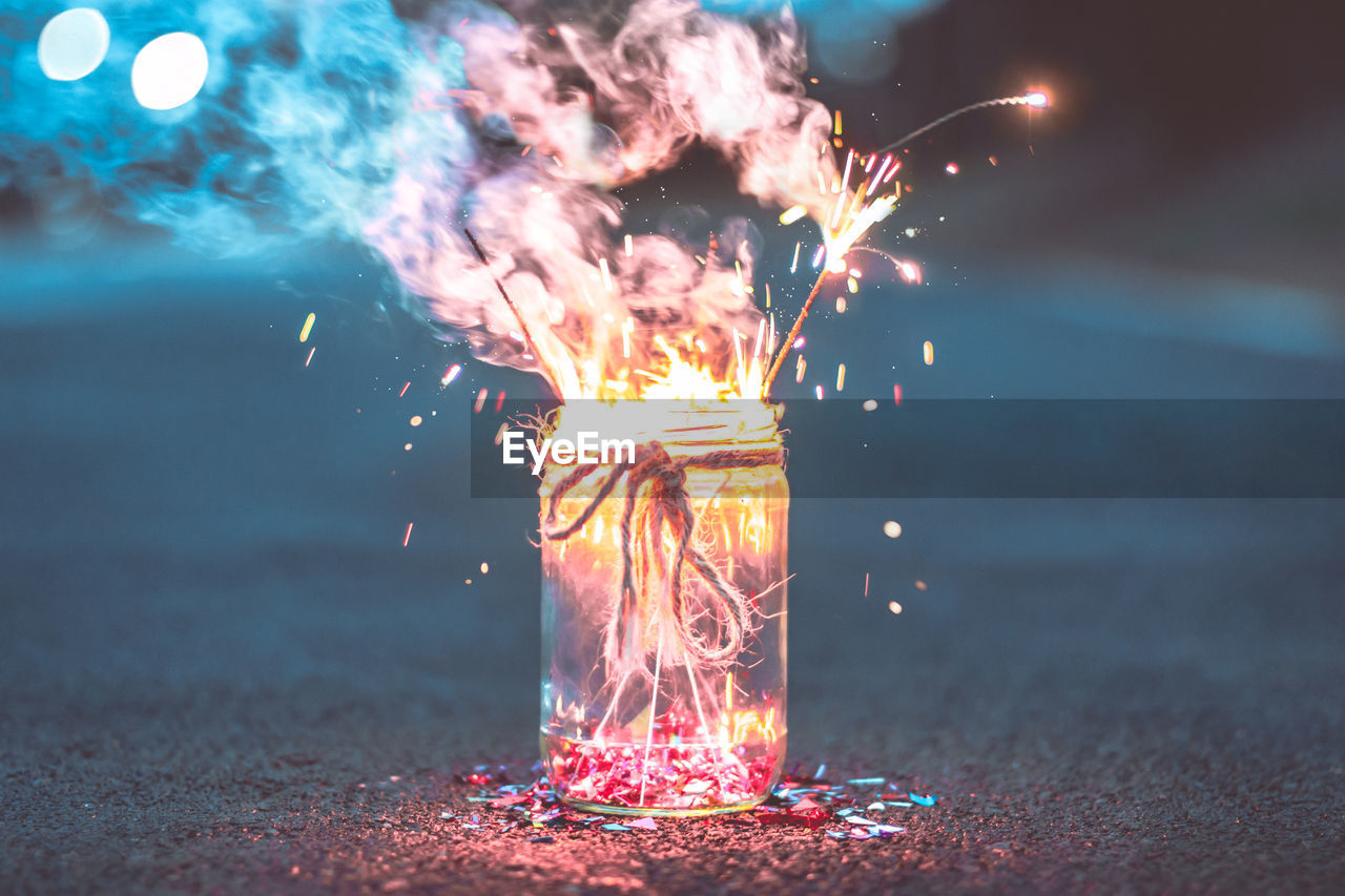 Close-up of sparklers burning in jar in road at night