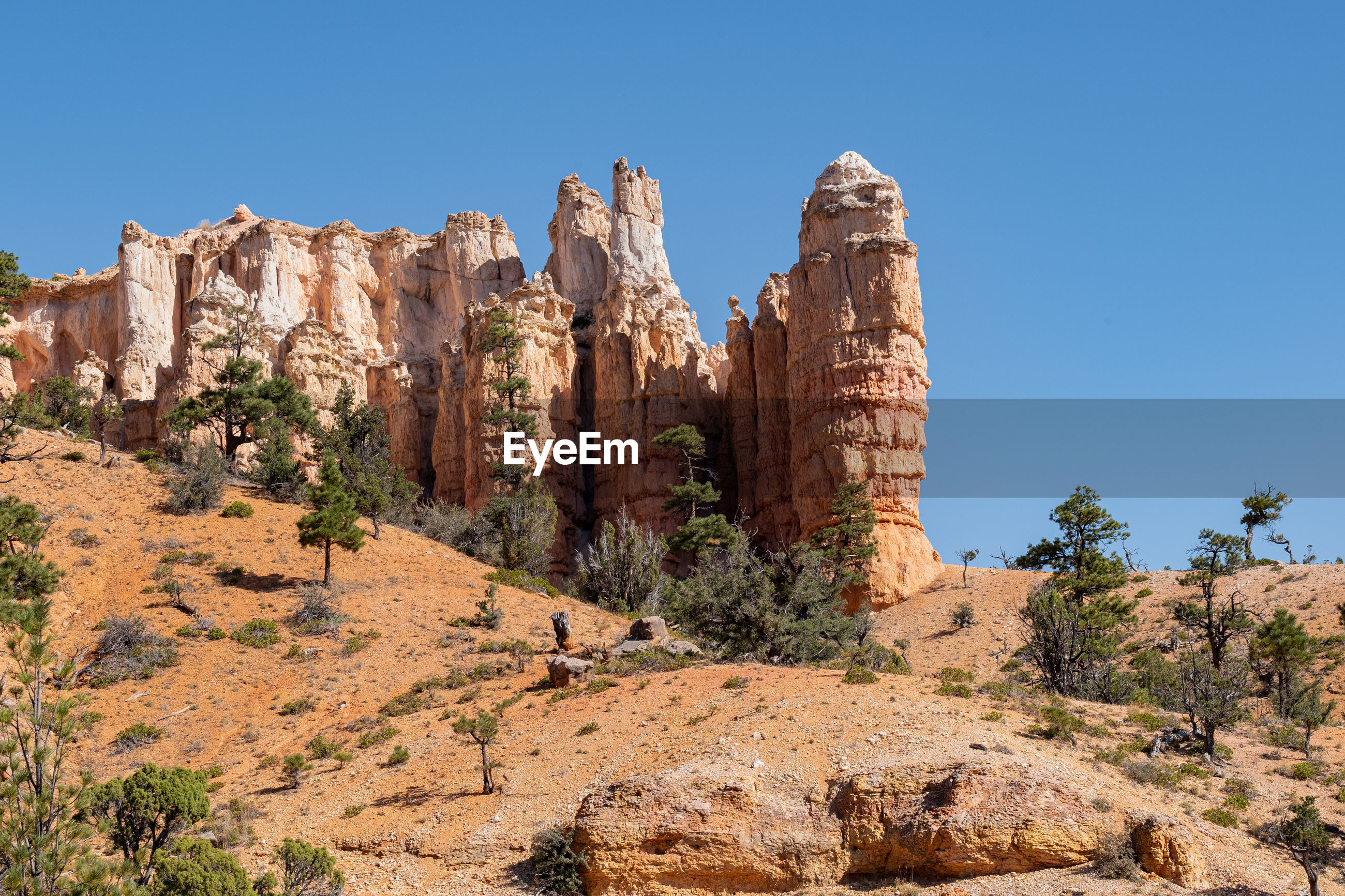 Panoramic view of rock formation against clear blue sky