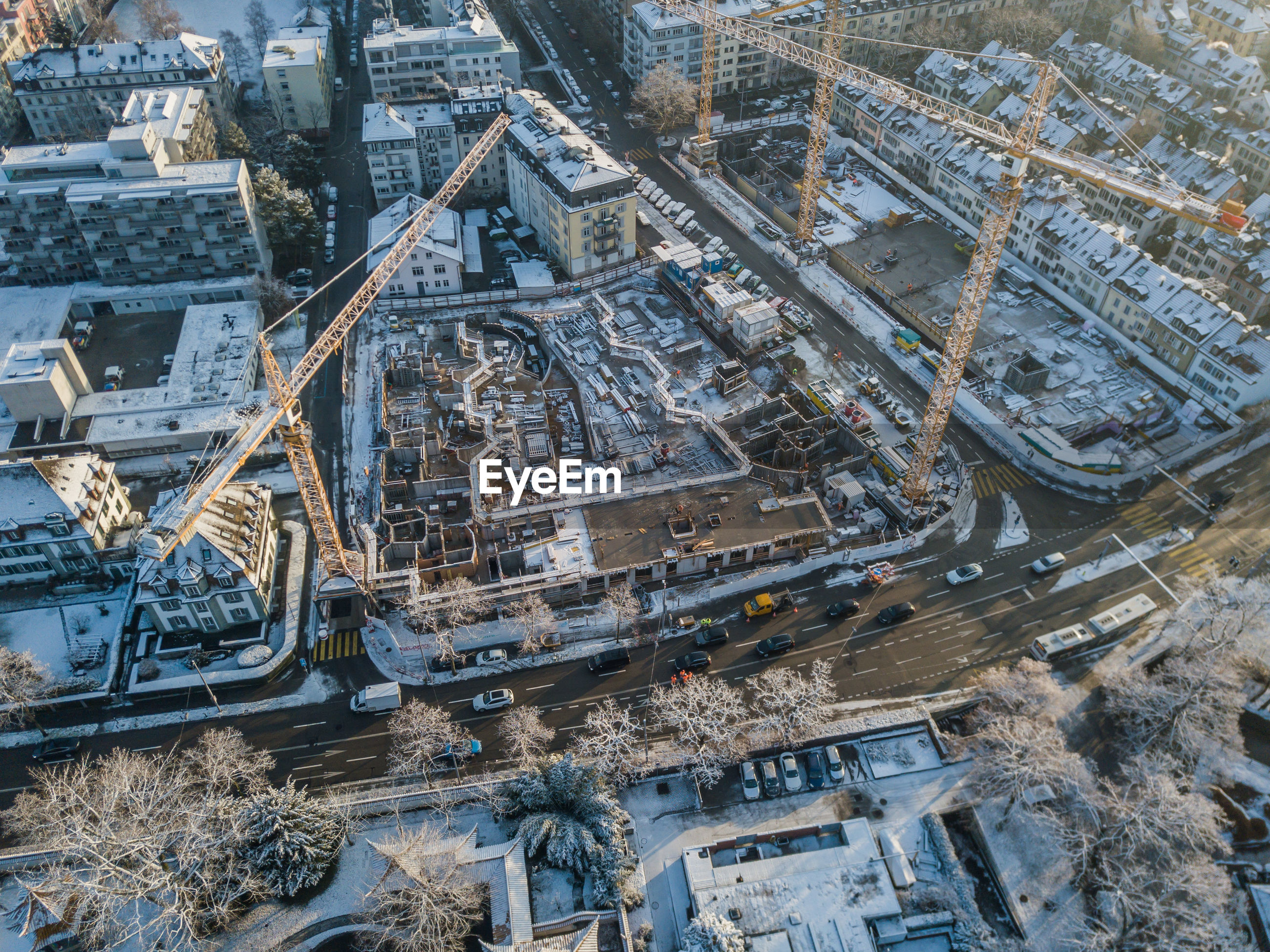 Aerial view of cranes and buildings in city during winter