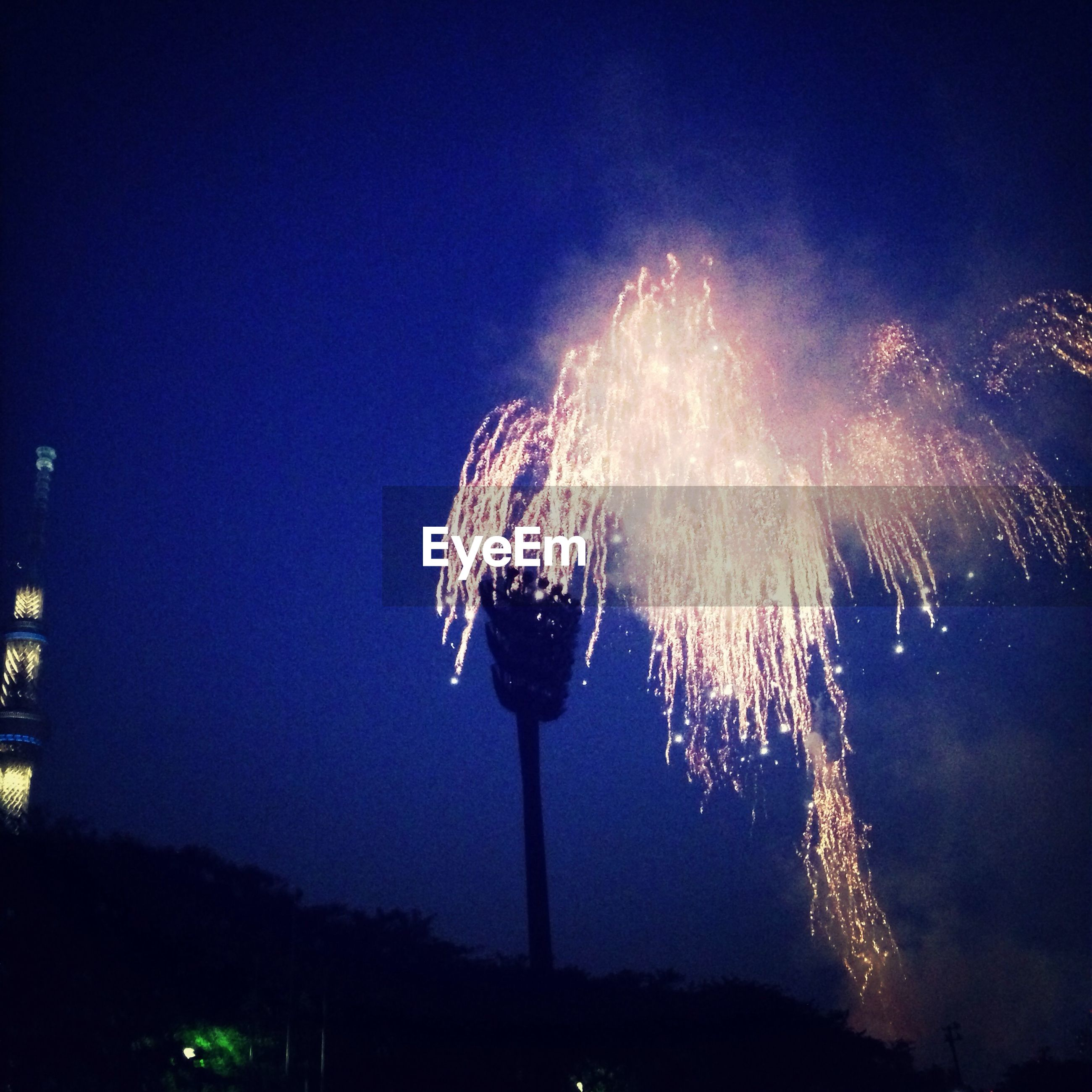night, illuminated, firework display, long exposure, motion, low angle view, arts culture and entertainment, exploding, firework - man made object, celebration, sparks, sky, glowing, blurred motion, event, building exterior, firework, entertainment, smoke - physical structure, clear sky