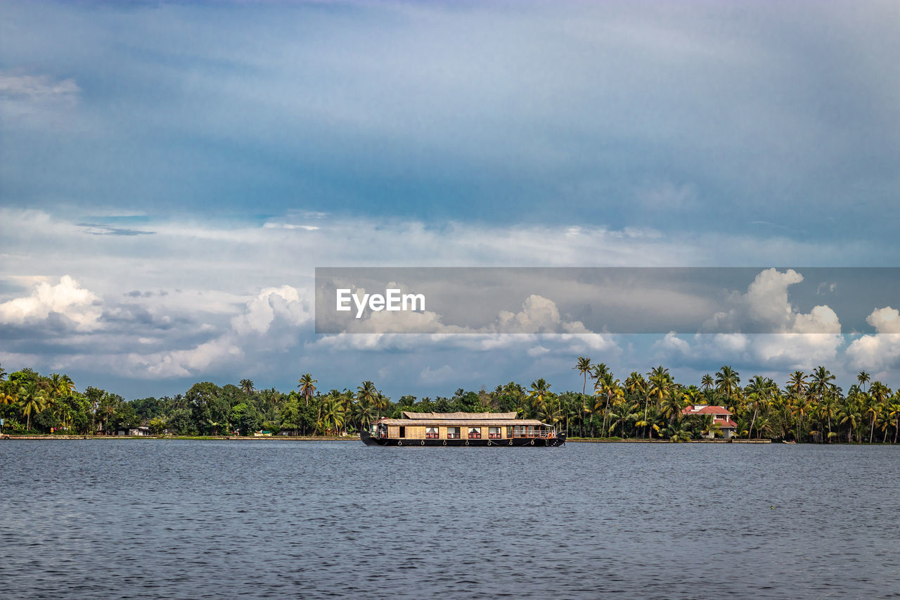 cloud - sky, sky, water, tree, waterfront, plant, beauty in nature, scenics - nature, tranquil scene, tranquility, nature, day, no people, nautical vessel, non-urban scene, transportation, river, idyllic, outdoors, boathouse
