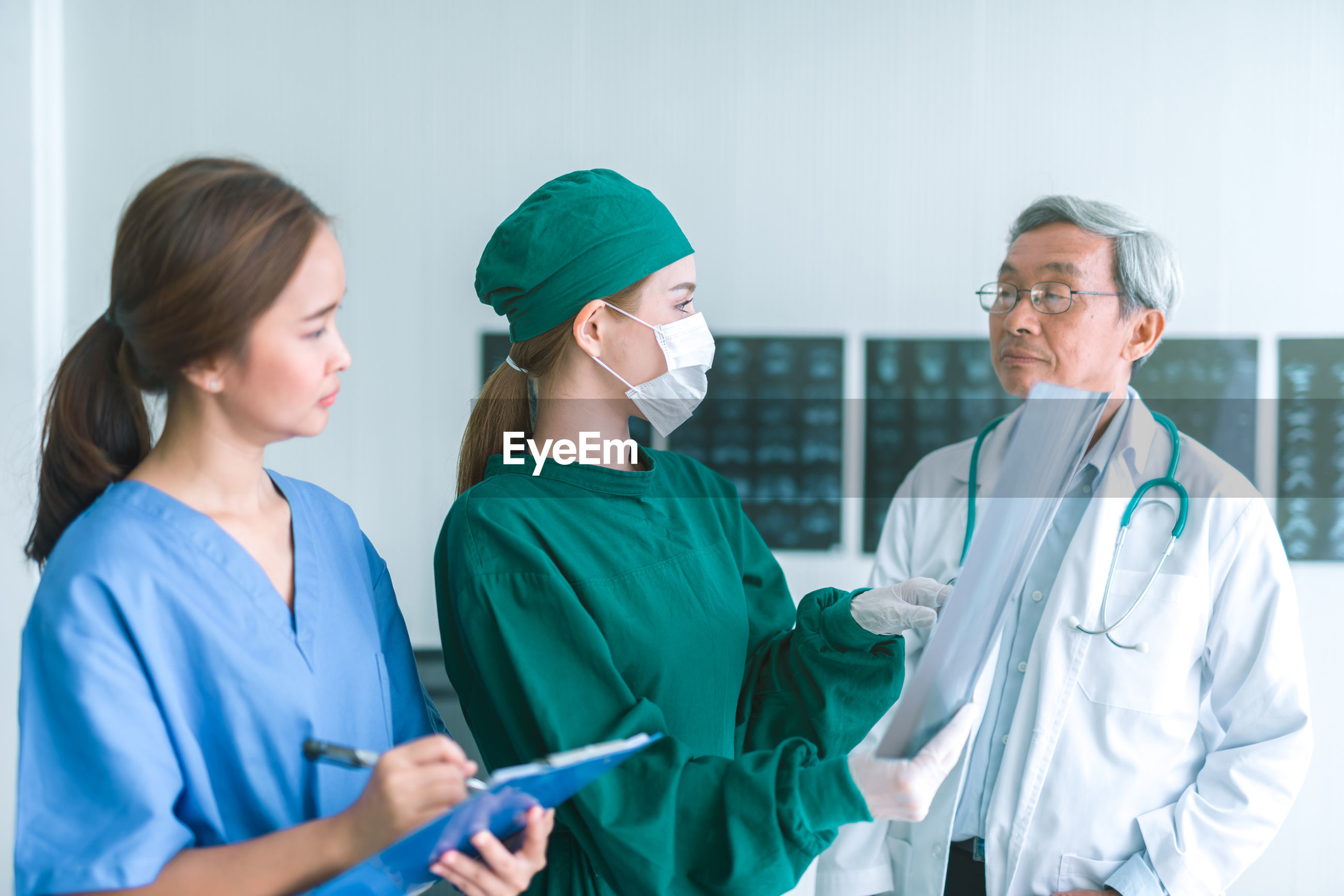 Doctors and nurse discussing while standing in hospital