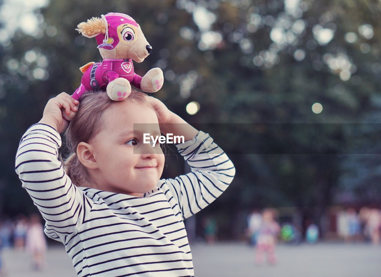 Close-Up Of Cute Smiling Girl With Toy Standing In Park