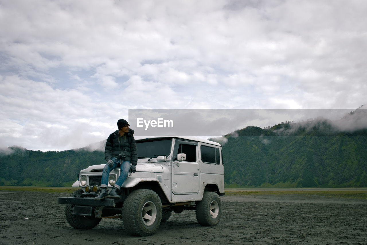 Full Length Of Hiker Sitting On Off-Road Car Against Cloudy Sky At Landscape