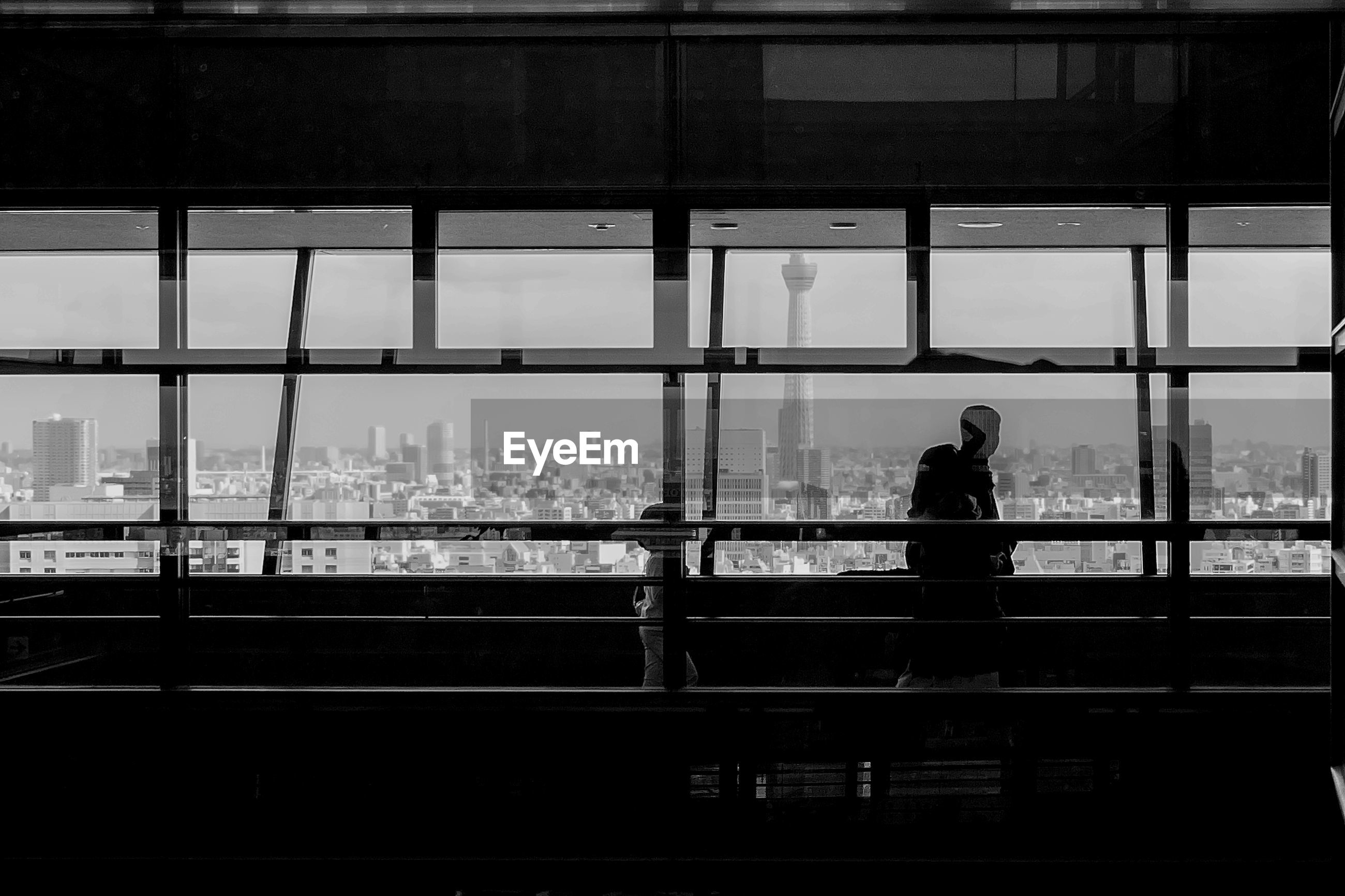 People seen through glass window walking in building