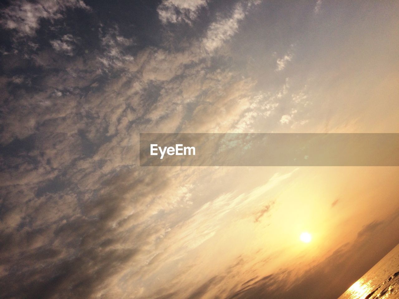 Tilt image of cloudy sky and sea during sunset