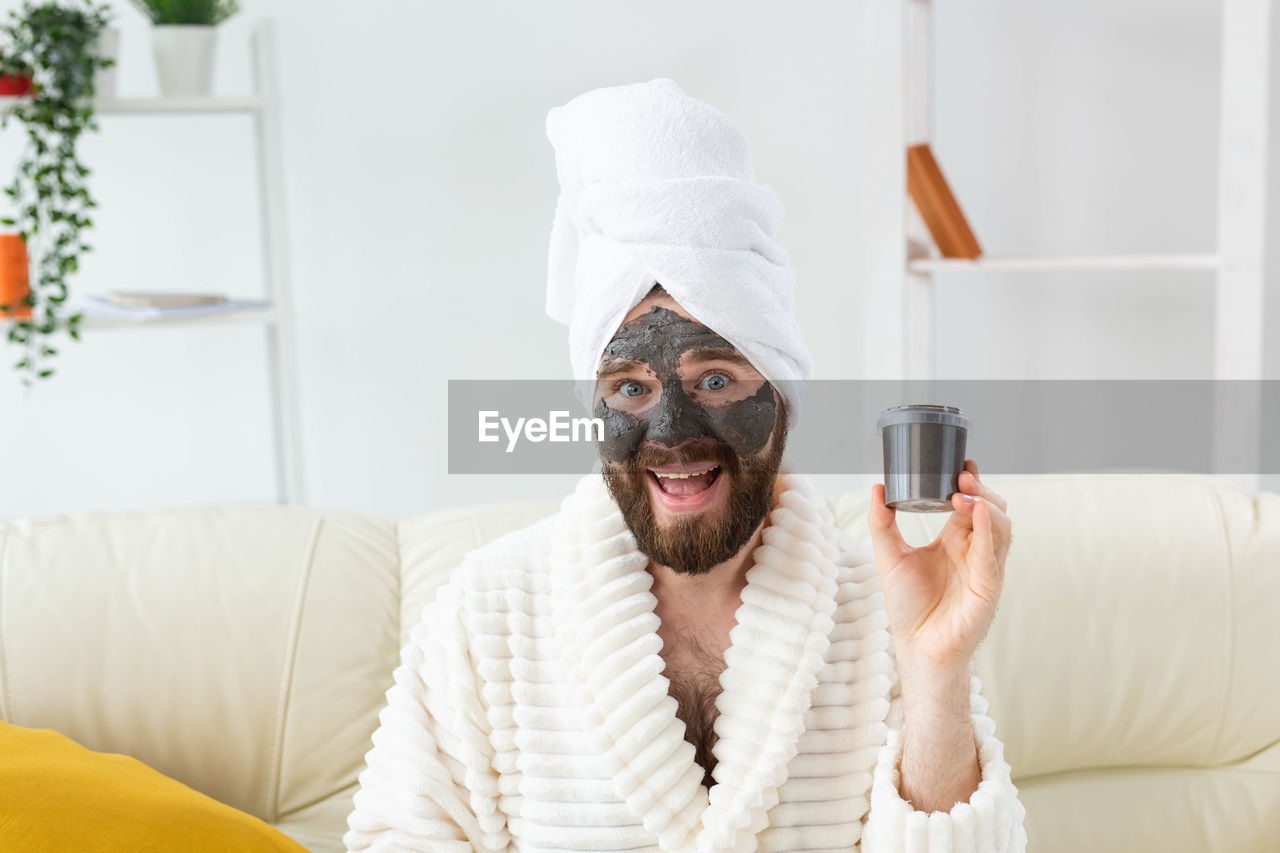 Portrait of young man applying facial mask at home