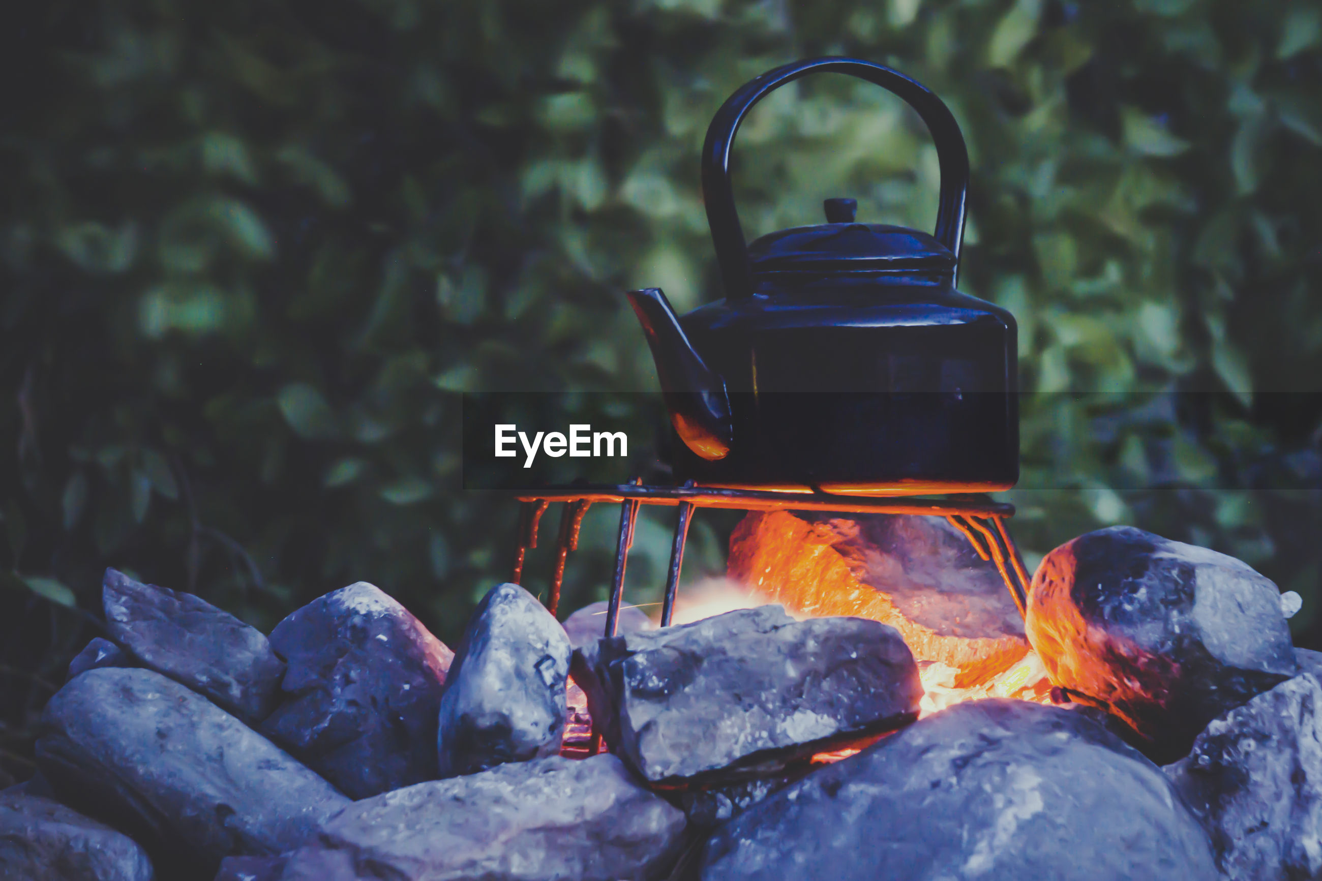 Adventure cooking during camping metal kettle boiling on a campfire, surrounded by stones