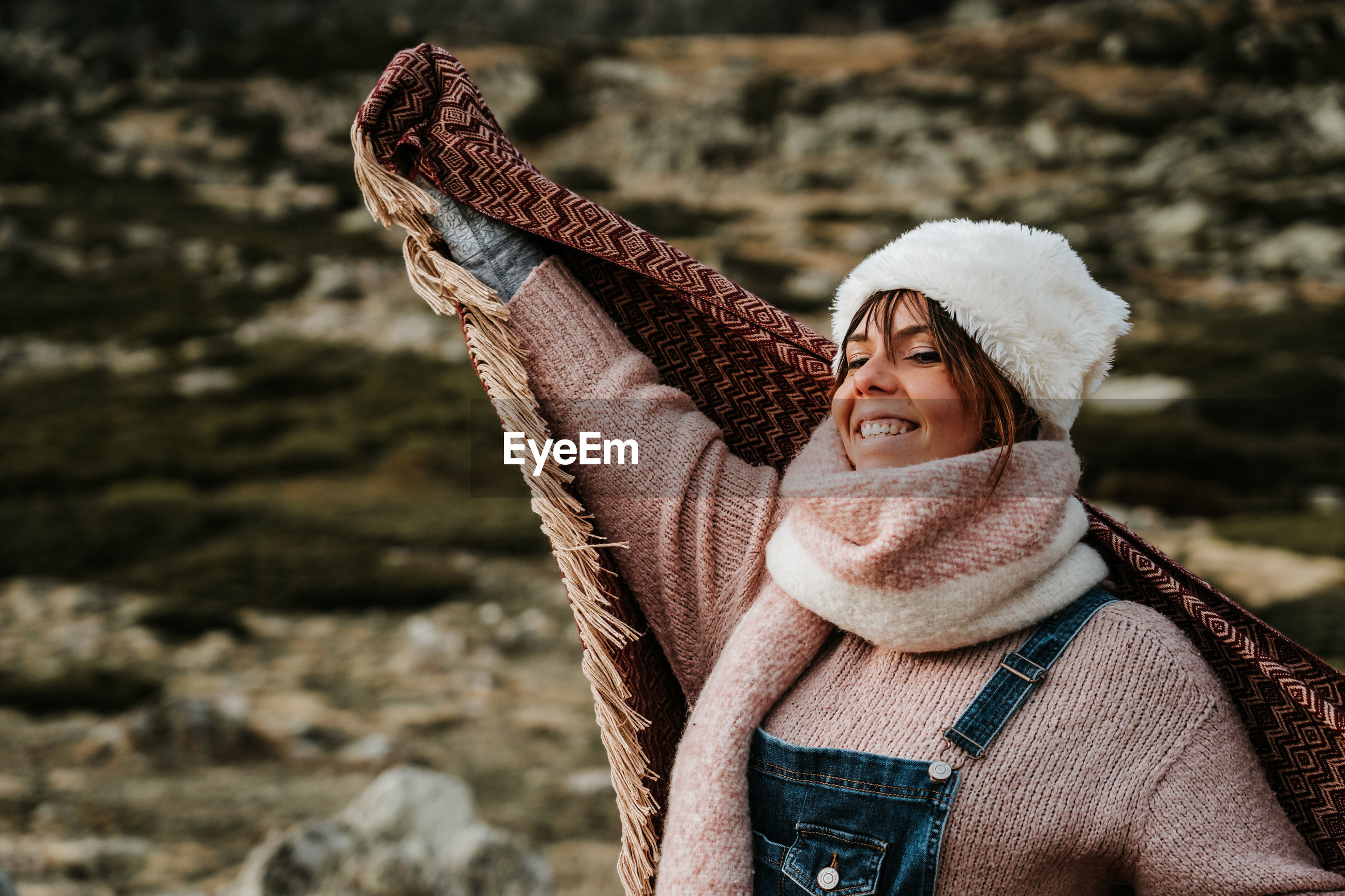 Smiling woman looking away while standing in warm clothing on mountain
