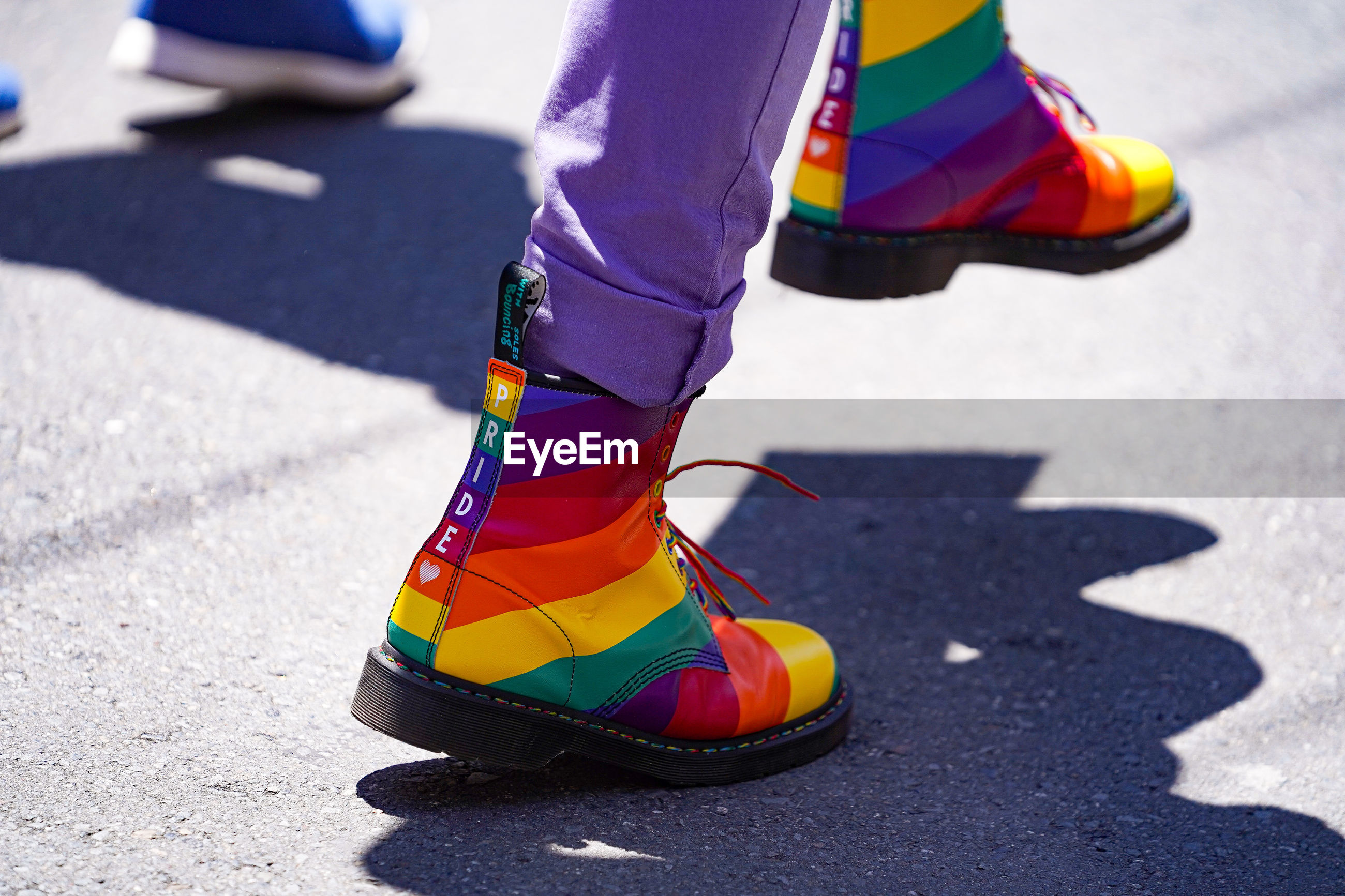 Low section of man walking with rainbow colored shoes on road