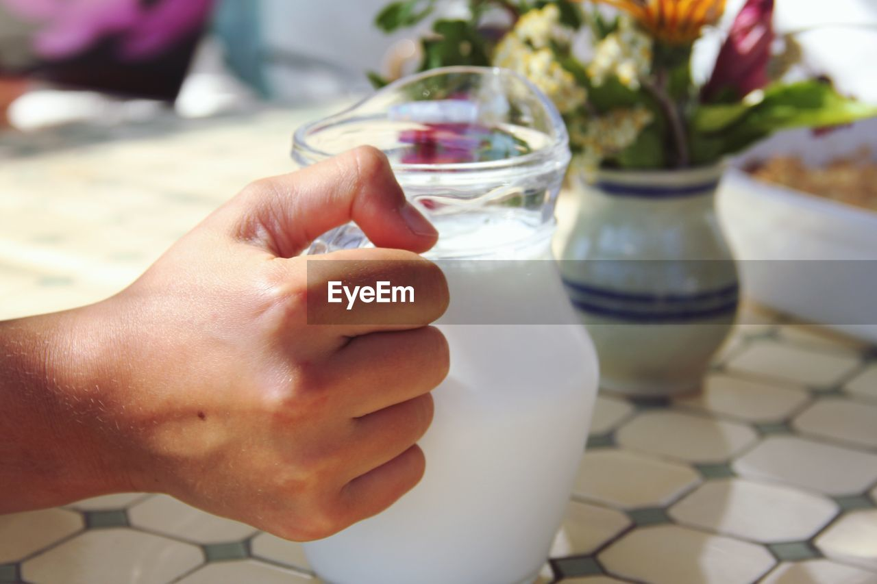 Cropped image of hand holding milk in jug on table