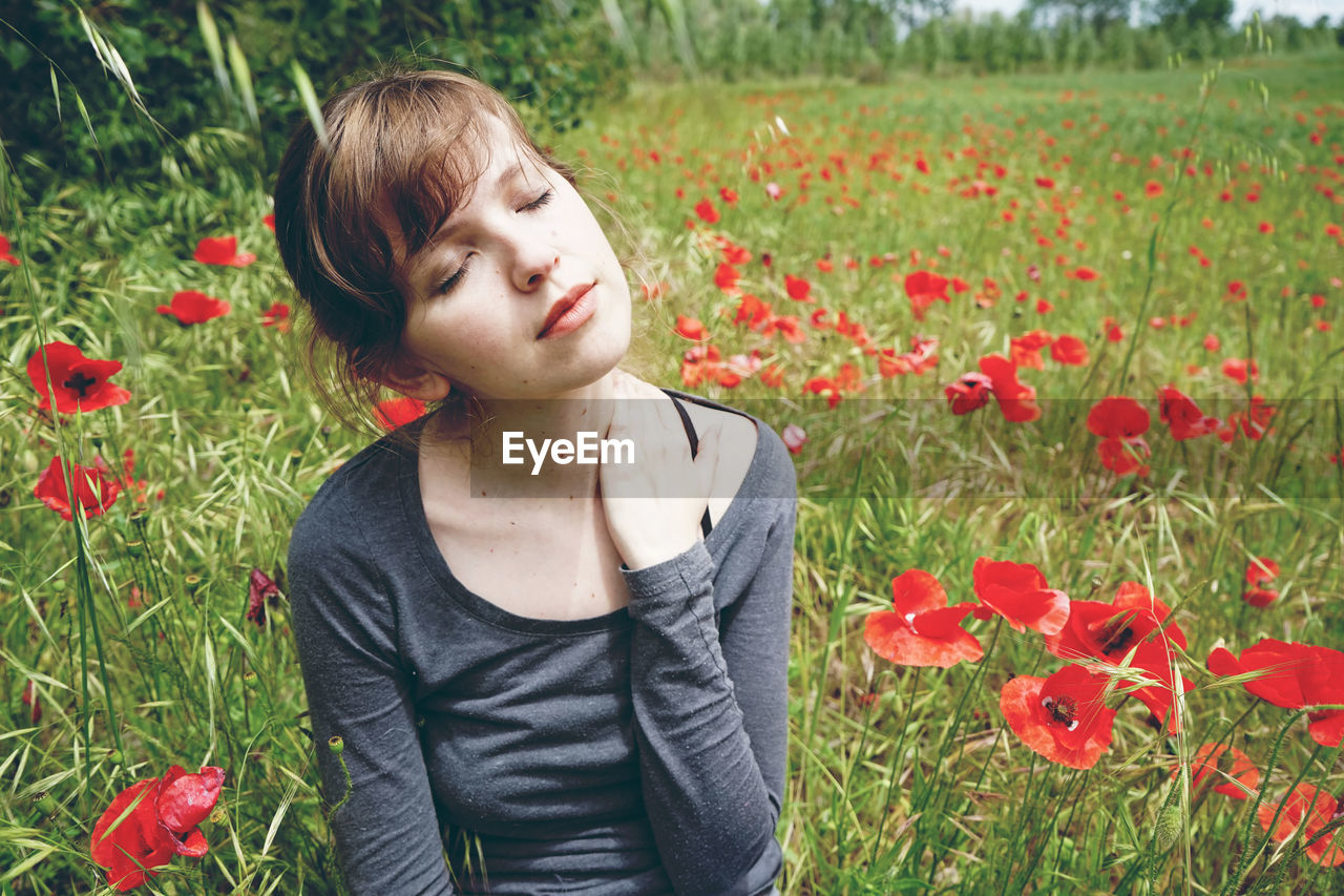 Woman With Eyes Closed Sitting Amidst Flowering Plants On Field