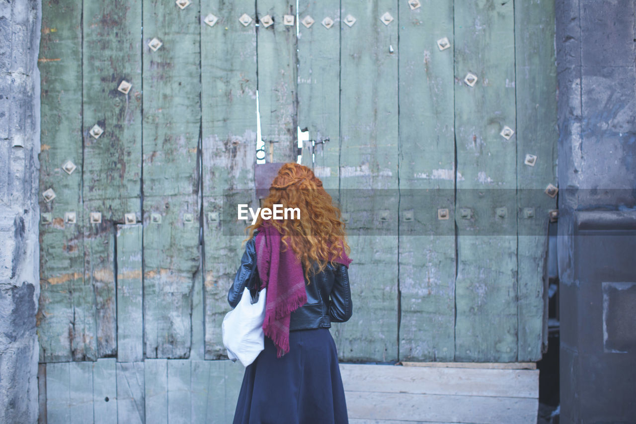 Rear View Of Woman Standing In Front Of Wooden Wall