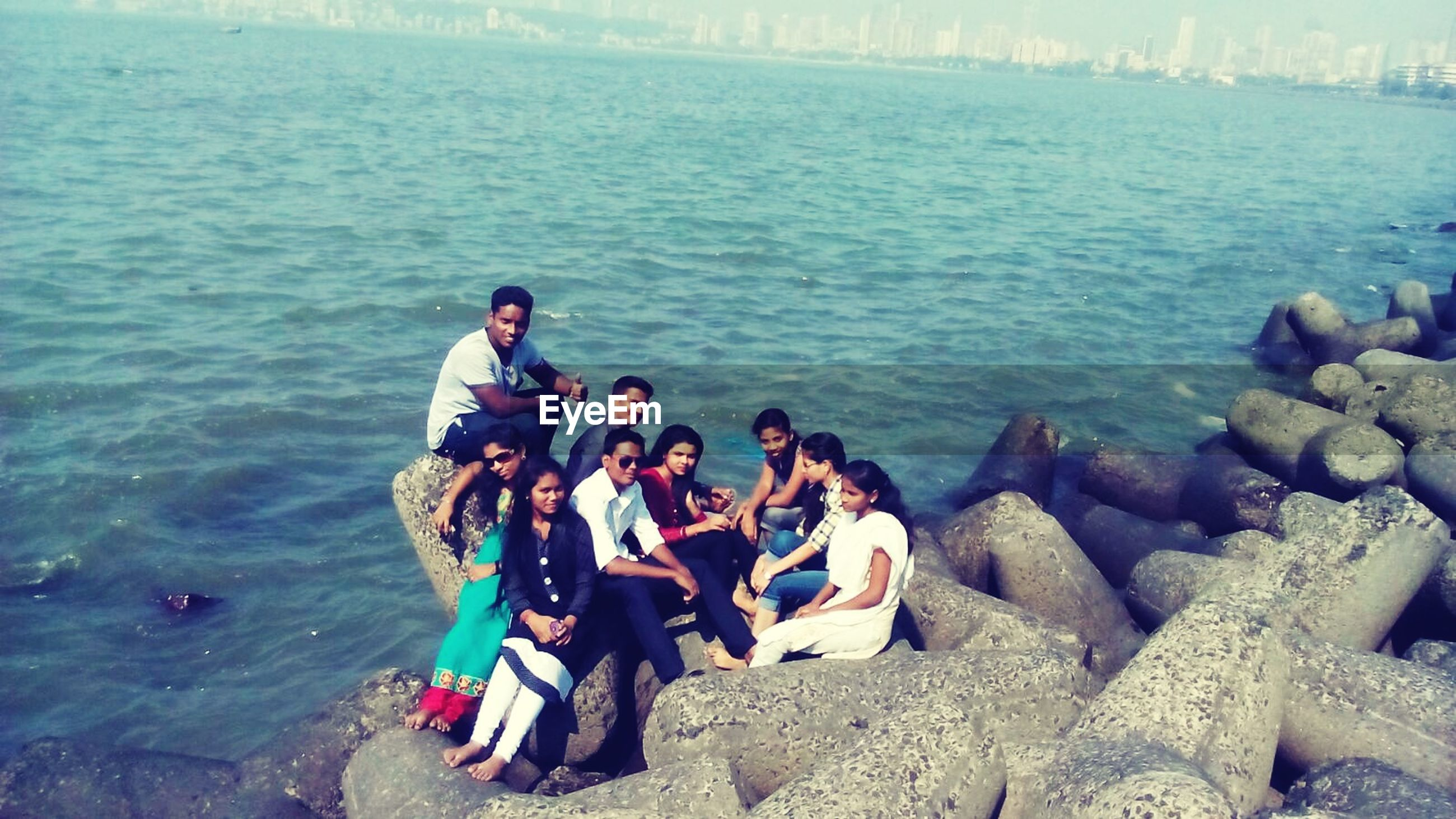 water, lifestyles, leisure activity, sea, vacations, men, togetherness, high angle view, rock - object, sitting, tourist, travel, nature, person, large group of people, casual clothing, transportation, tourism, weekend activities