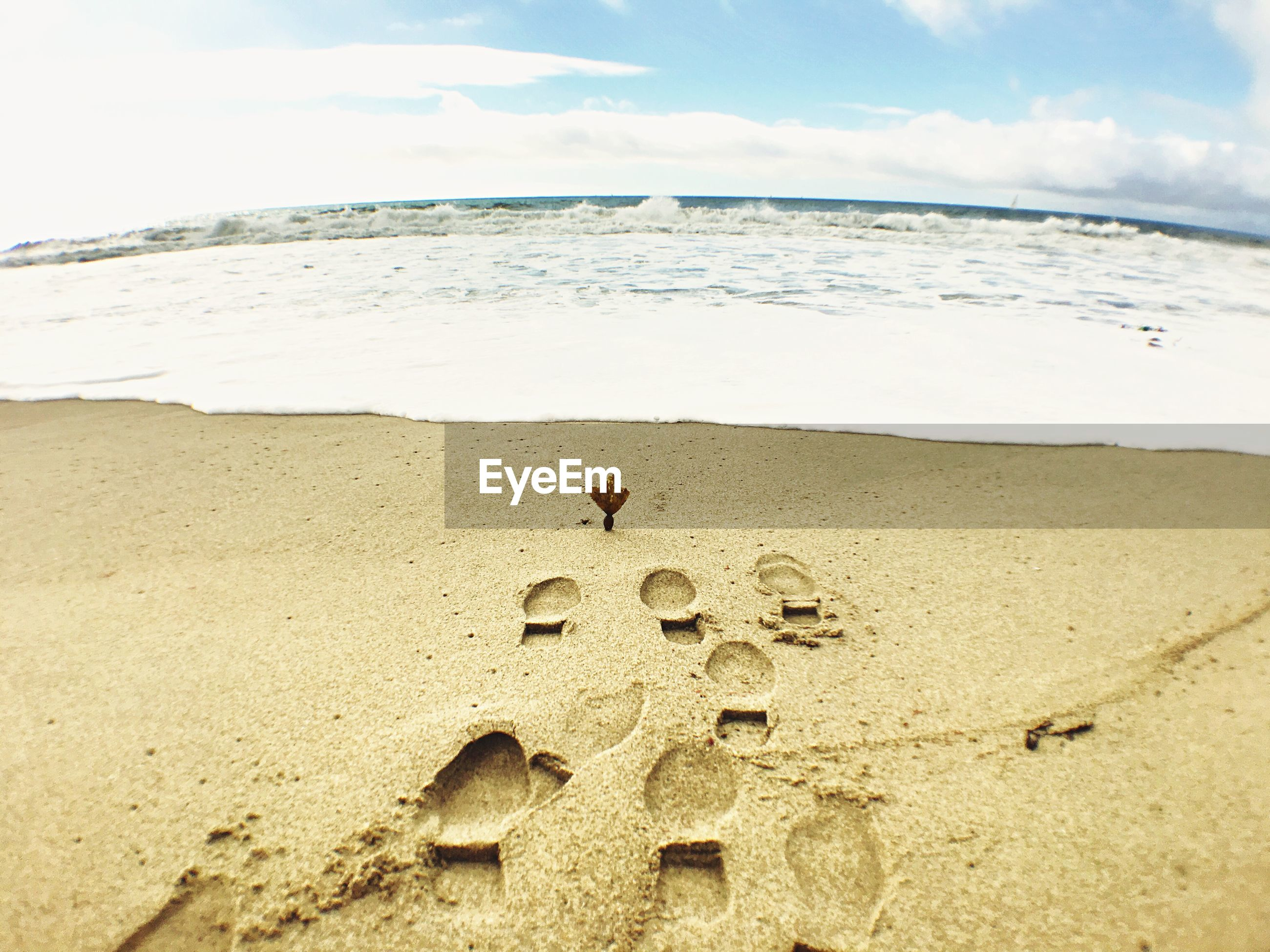 High angle view of footprints on shore by waves