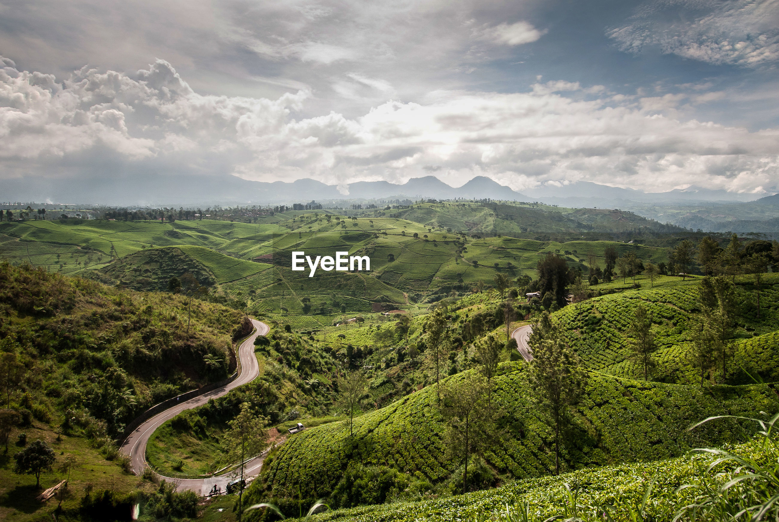 Scenic view of green hills against cloudy sky