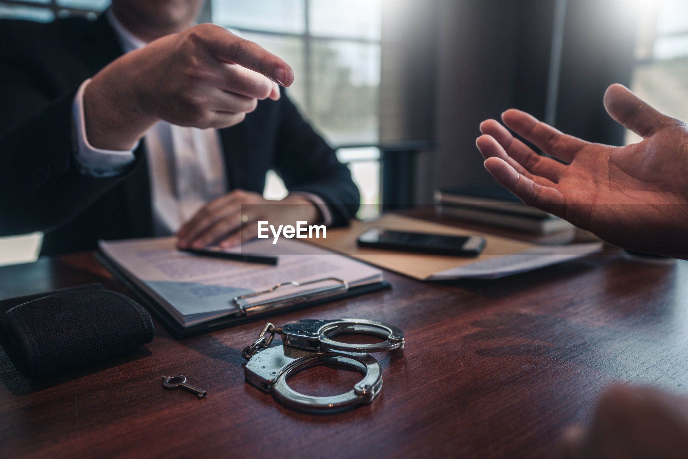 Midsection of man pointing at businessman sitting at table