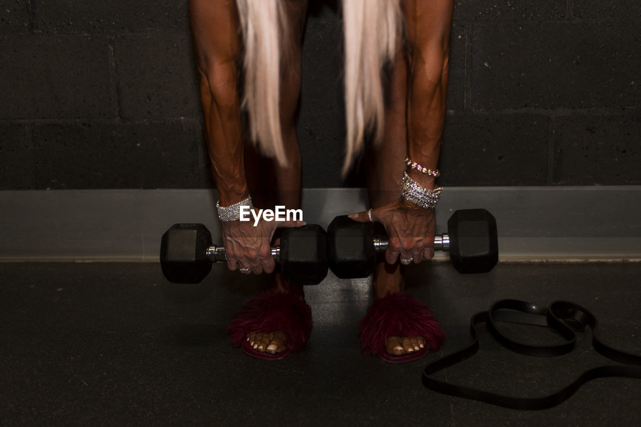 Low section of woman lifting dumbbells in gym