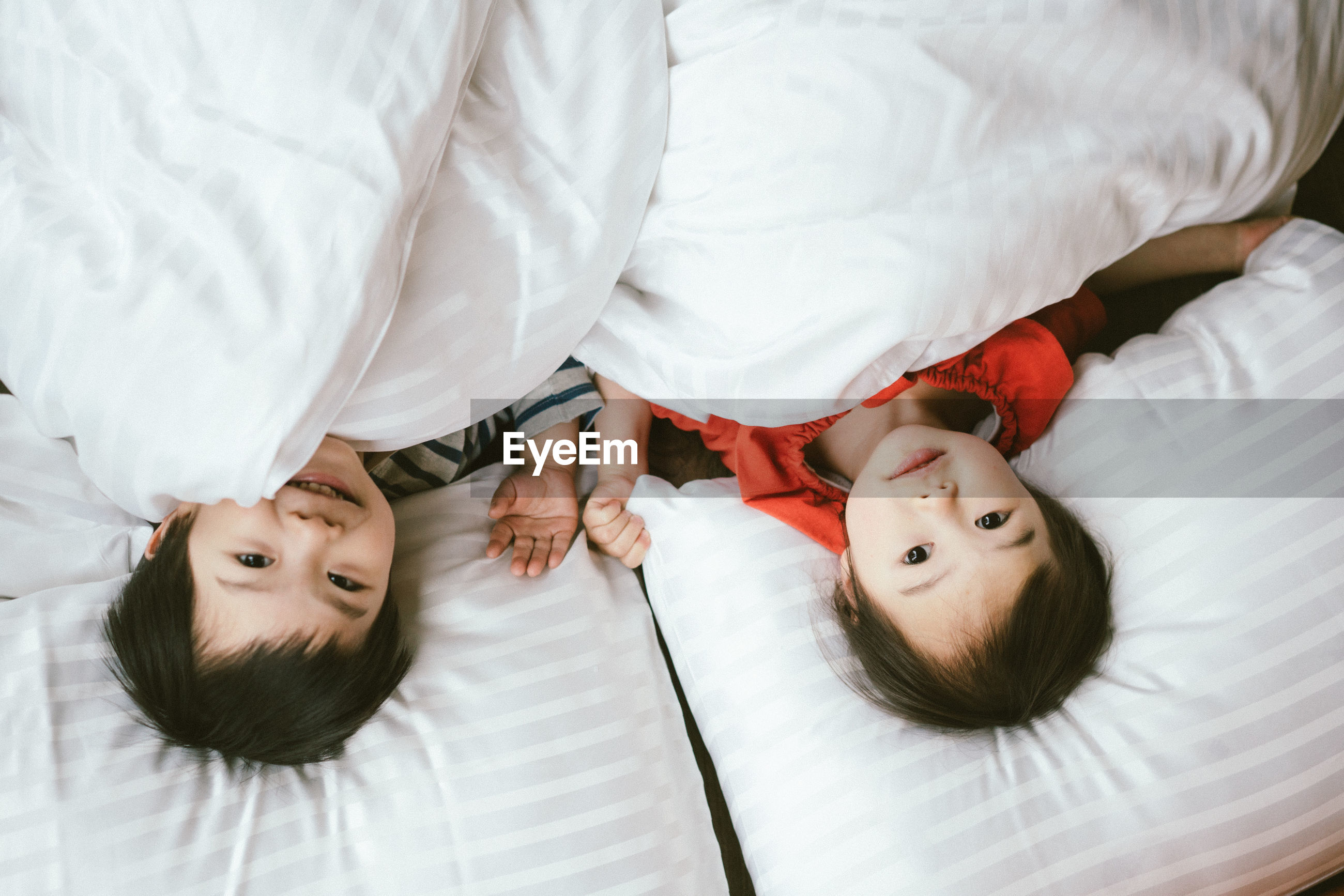 High angle portrait of siblings relaxing on bed at home