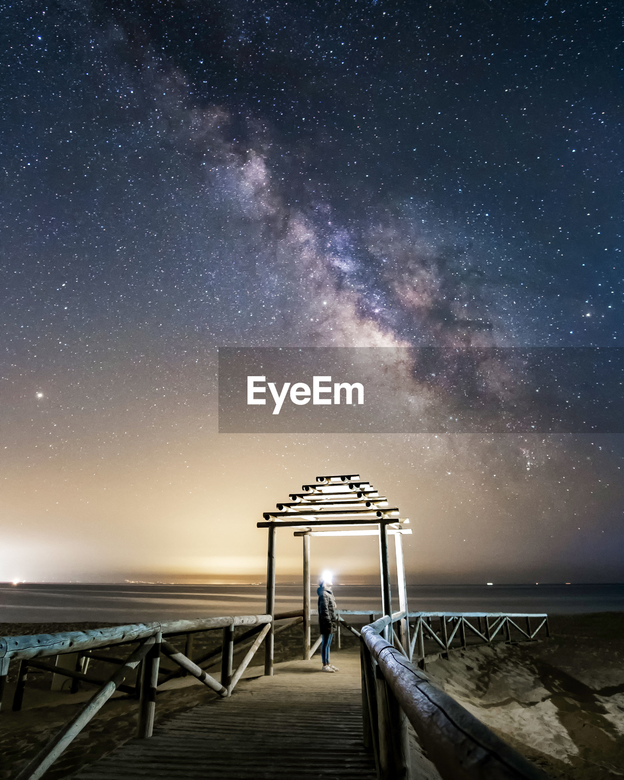 GAZEBO BY SEA AGAINST SKY AT NIGHT