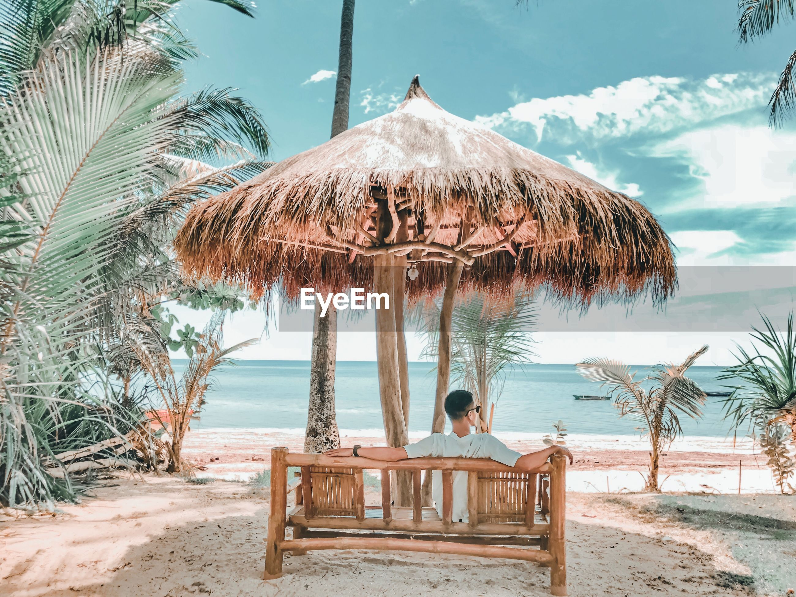 Rear view of young man relaxing on bench at beach against sky