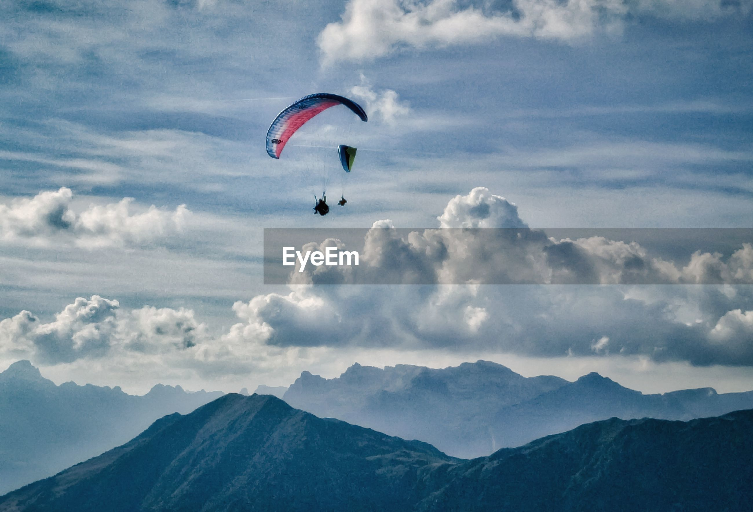 People paragliding above mountains against cloudy sky