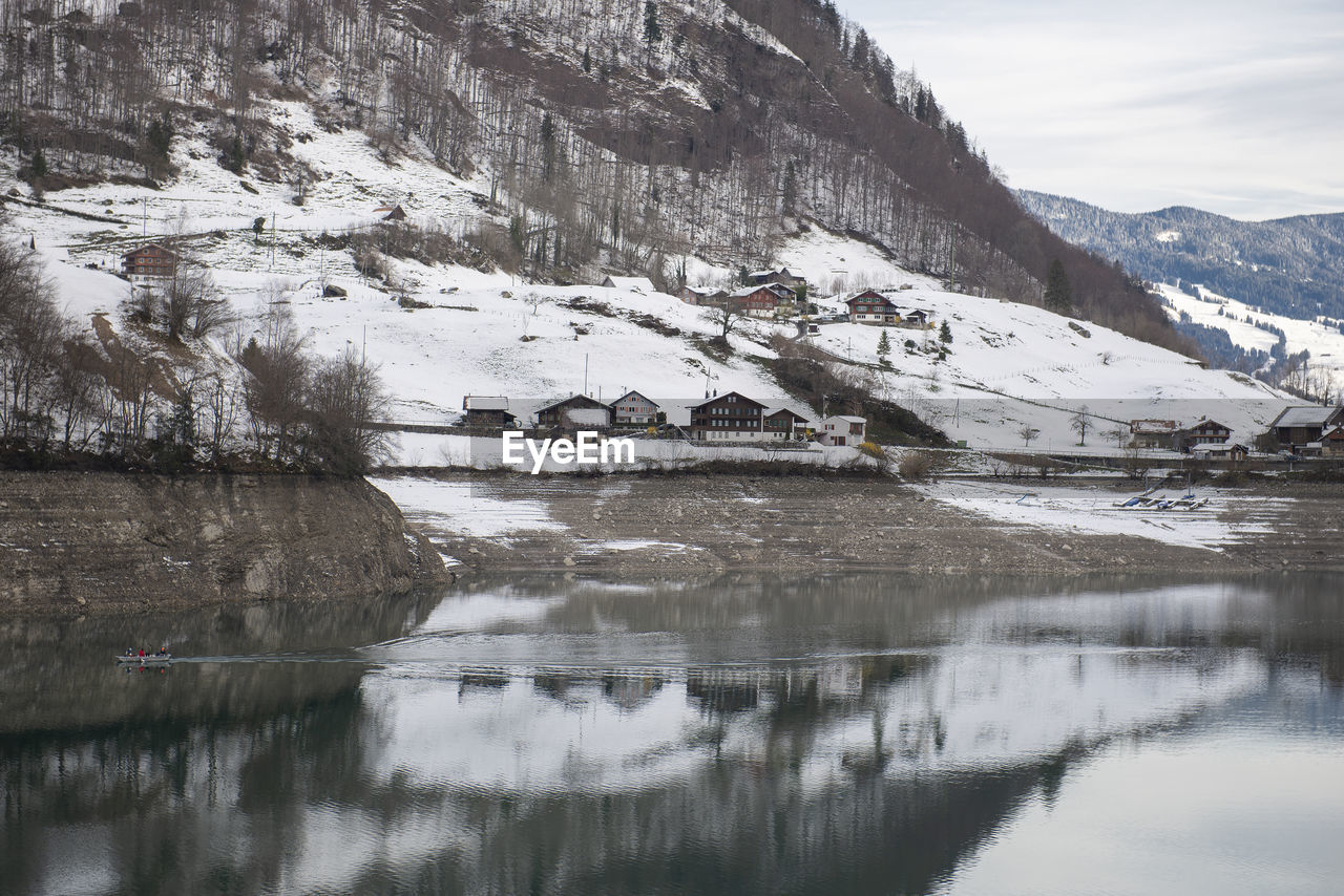 cold temperature, mountain, winter, water, snow, building exterior, architecture, built structure, scenics - nature, waterfront, beauty in nature, building, house, reflection, day, environment, nature, no people, outdoors, snowcapped mountain