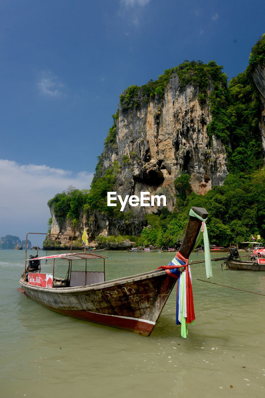 Boat Moored On Shore Against Mountains