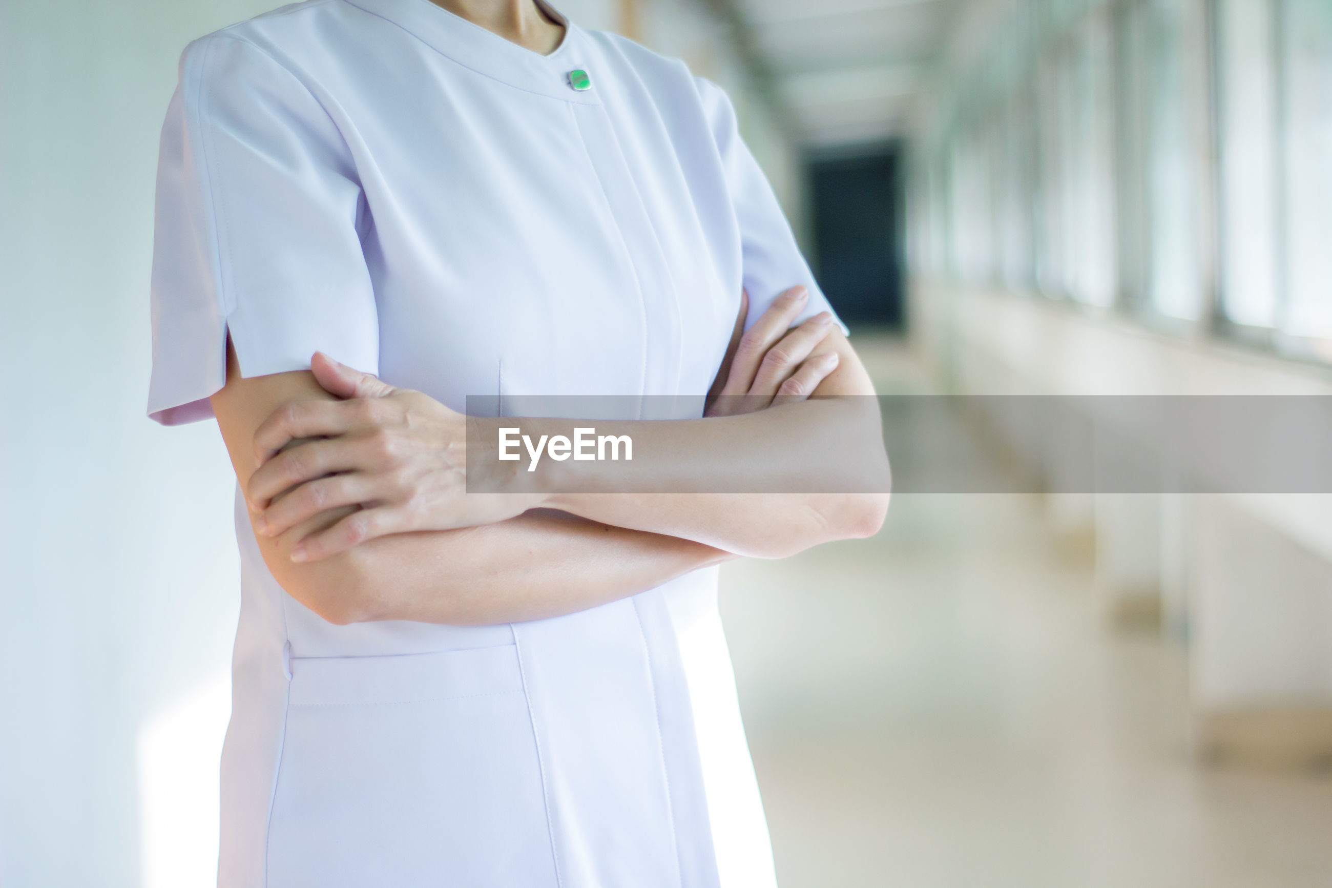 Midsection of nurse with arms crossed standing in corridor