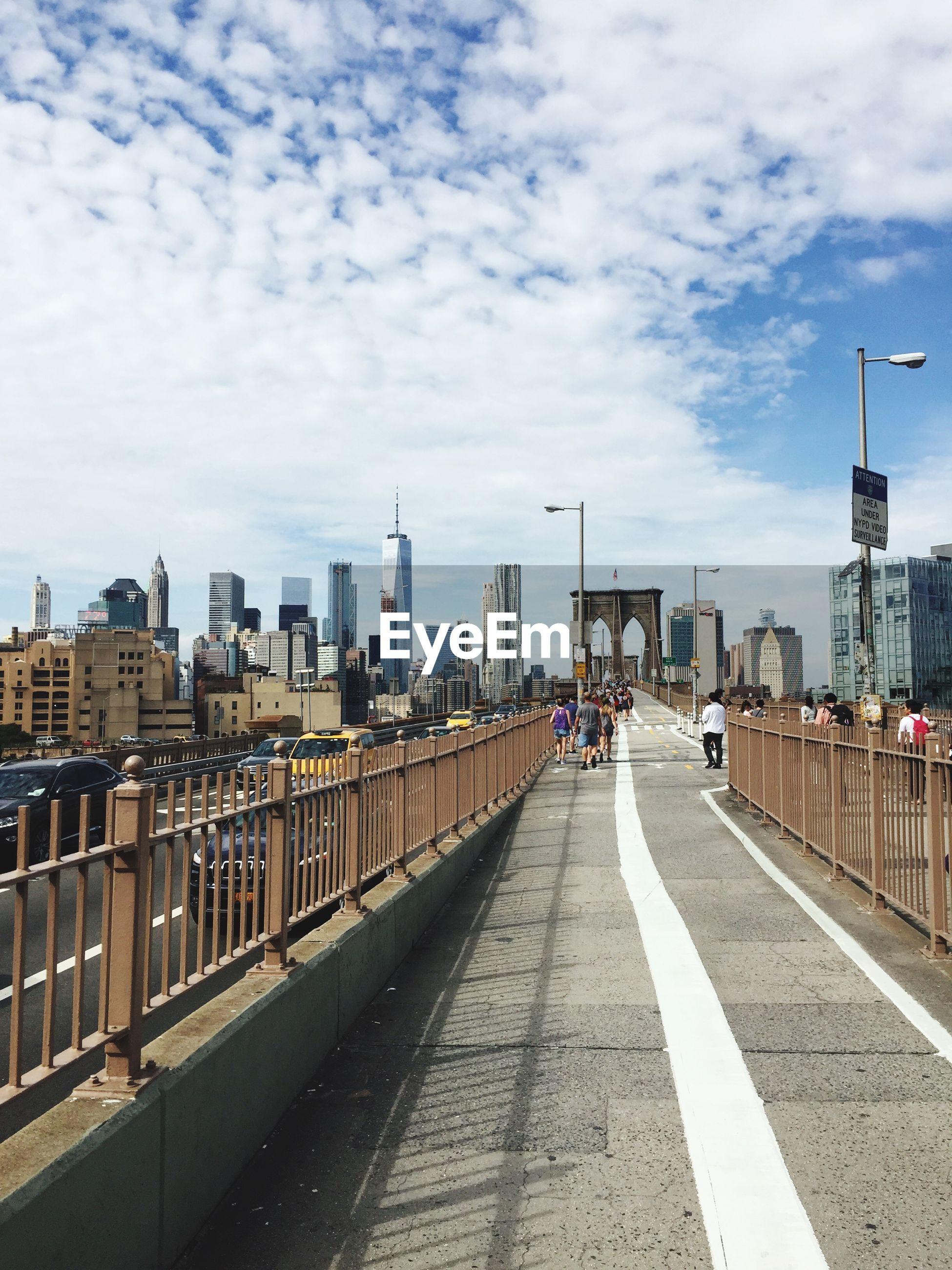 People on brooklyn bridge against city skyline