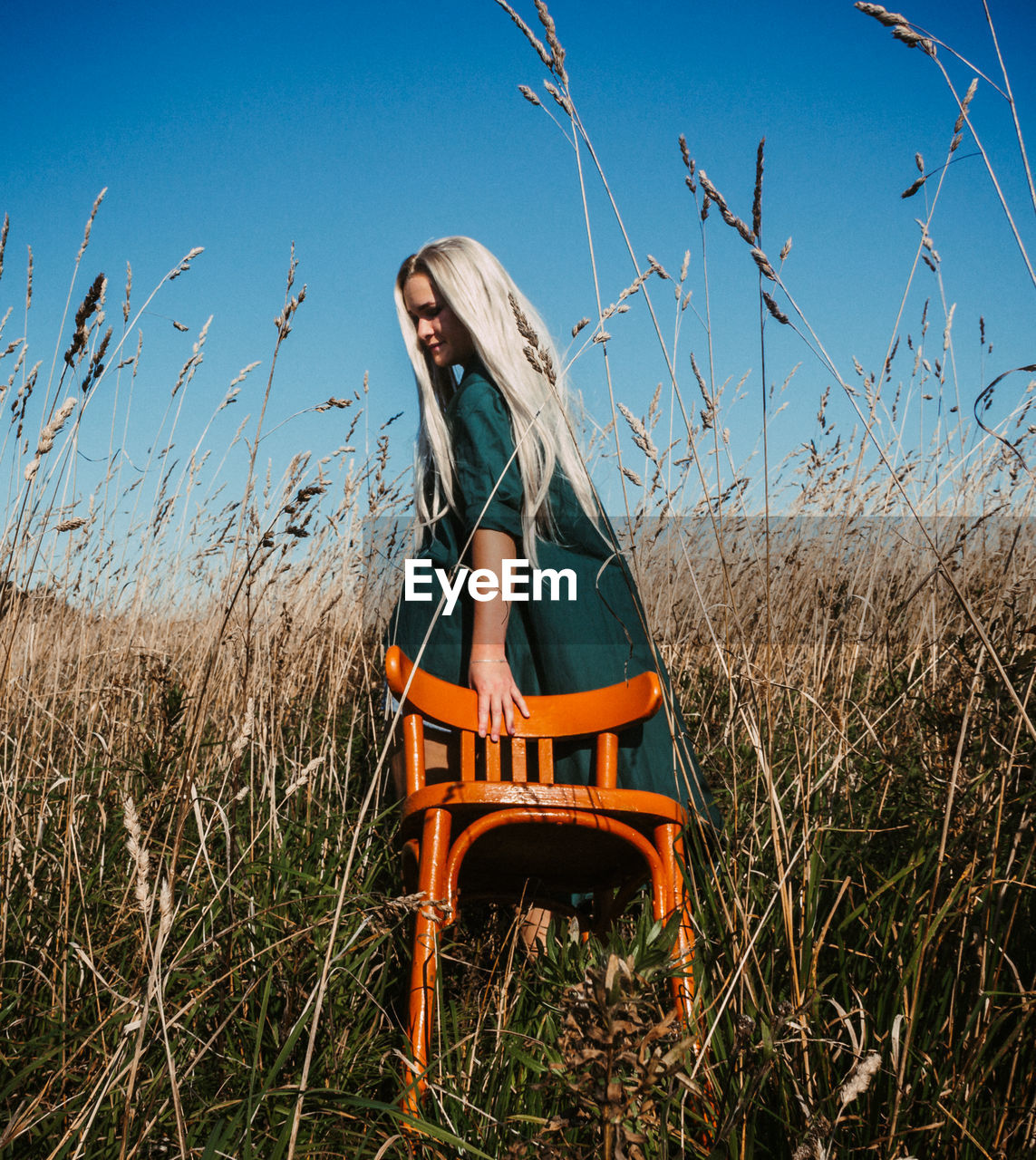 Beautiful woman with chair amidst grass