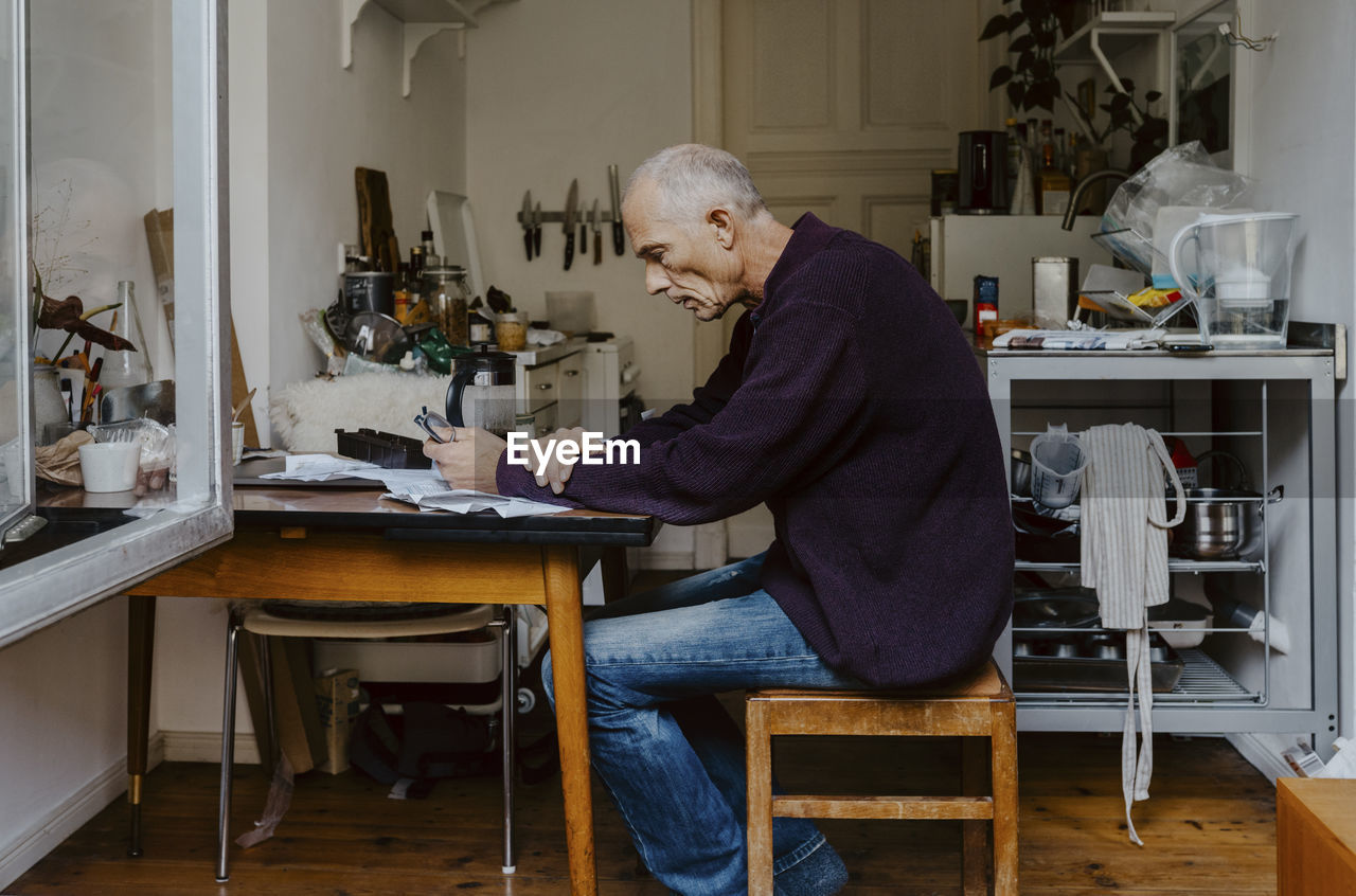 SIDE VIEW OF MAN WORKING ON TABLE IN CAFE