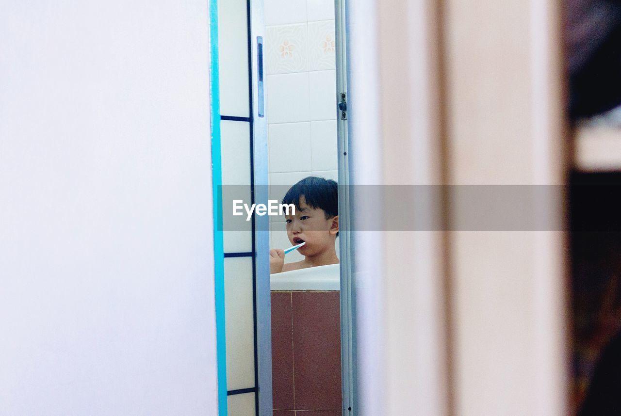 Cute boy brushing teeth in bathroom at home