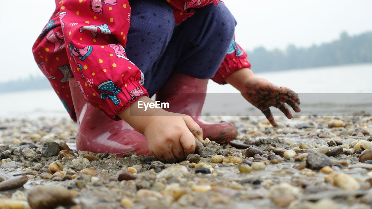 Midsection Of Girl Playing On Pebble Beach