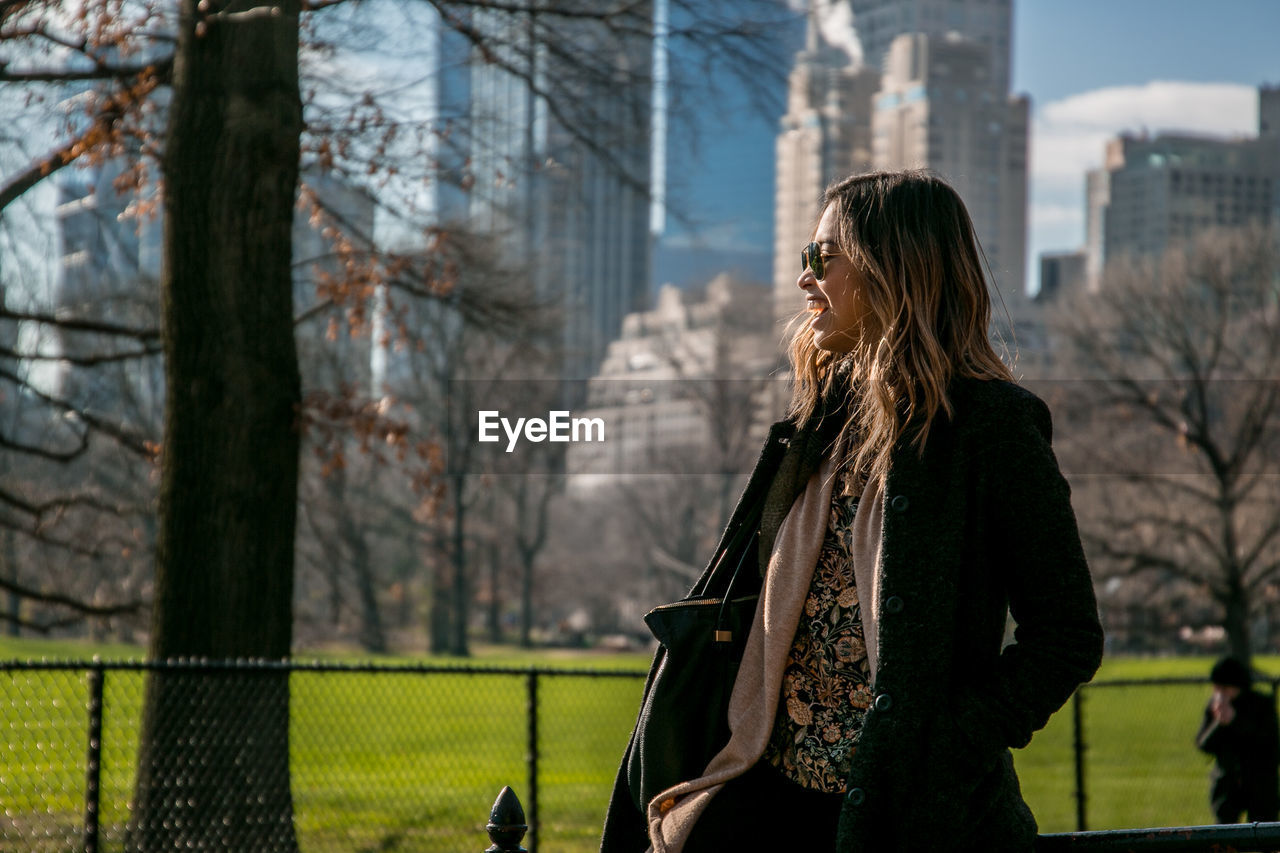 Happy Woman Wearing Jacket Standing By Trees And Buildings