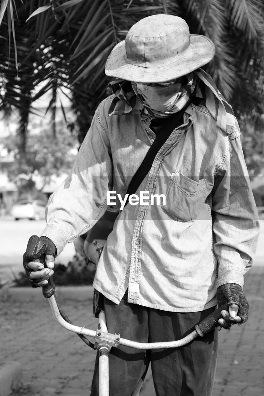 Man wearing mask with equipment standing against tree