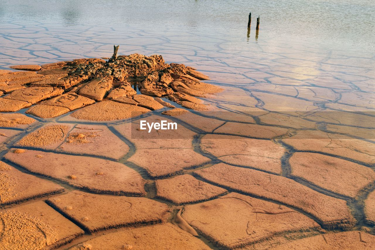 water, nature, no people, high angle view, scenics - nature, day, tranquility, land, dry, lake, outdoors, non-urban scene, climate, drought, arid climate, beauty in nature, tranquil scene, cracked, sunlight, mud