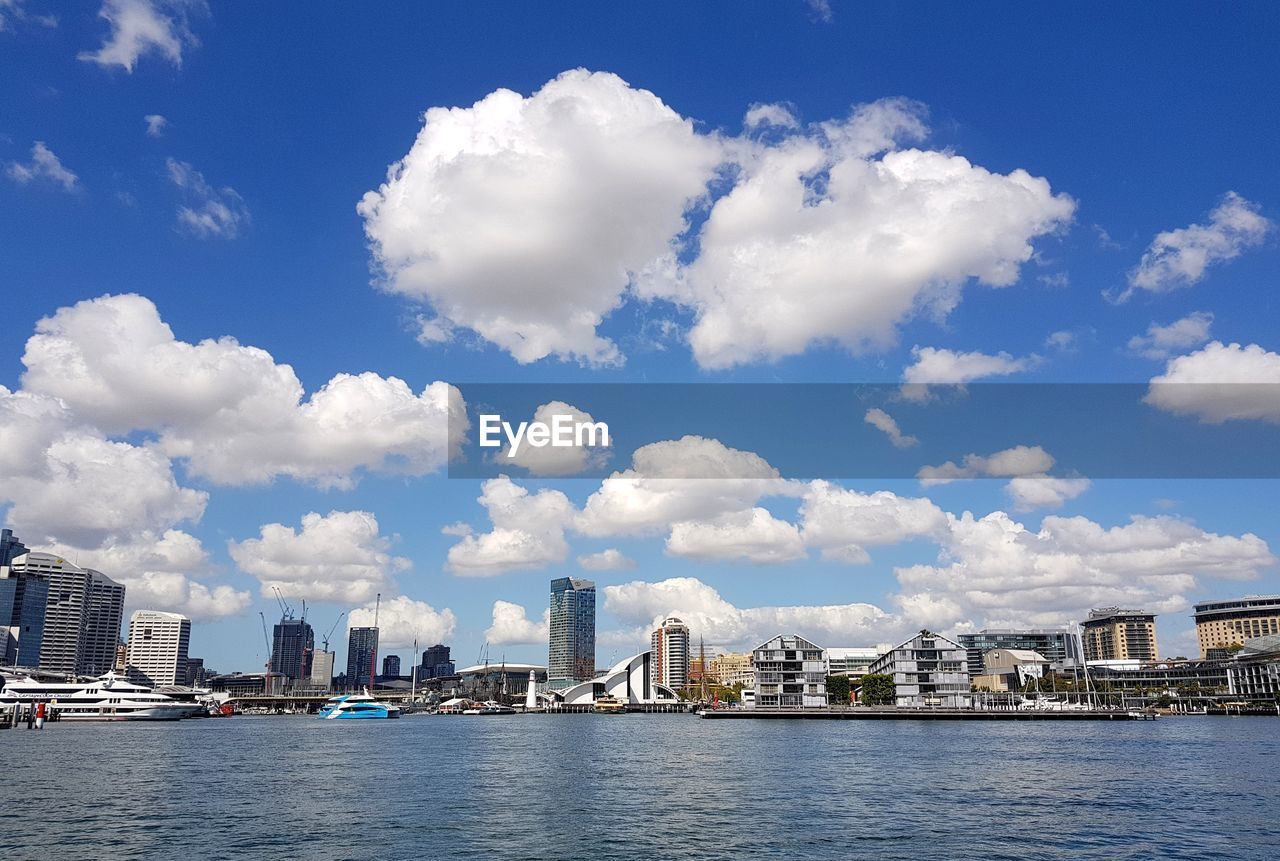 MODERN BUILDINGS BY RIVER AGAINST SKY