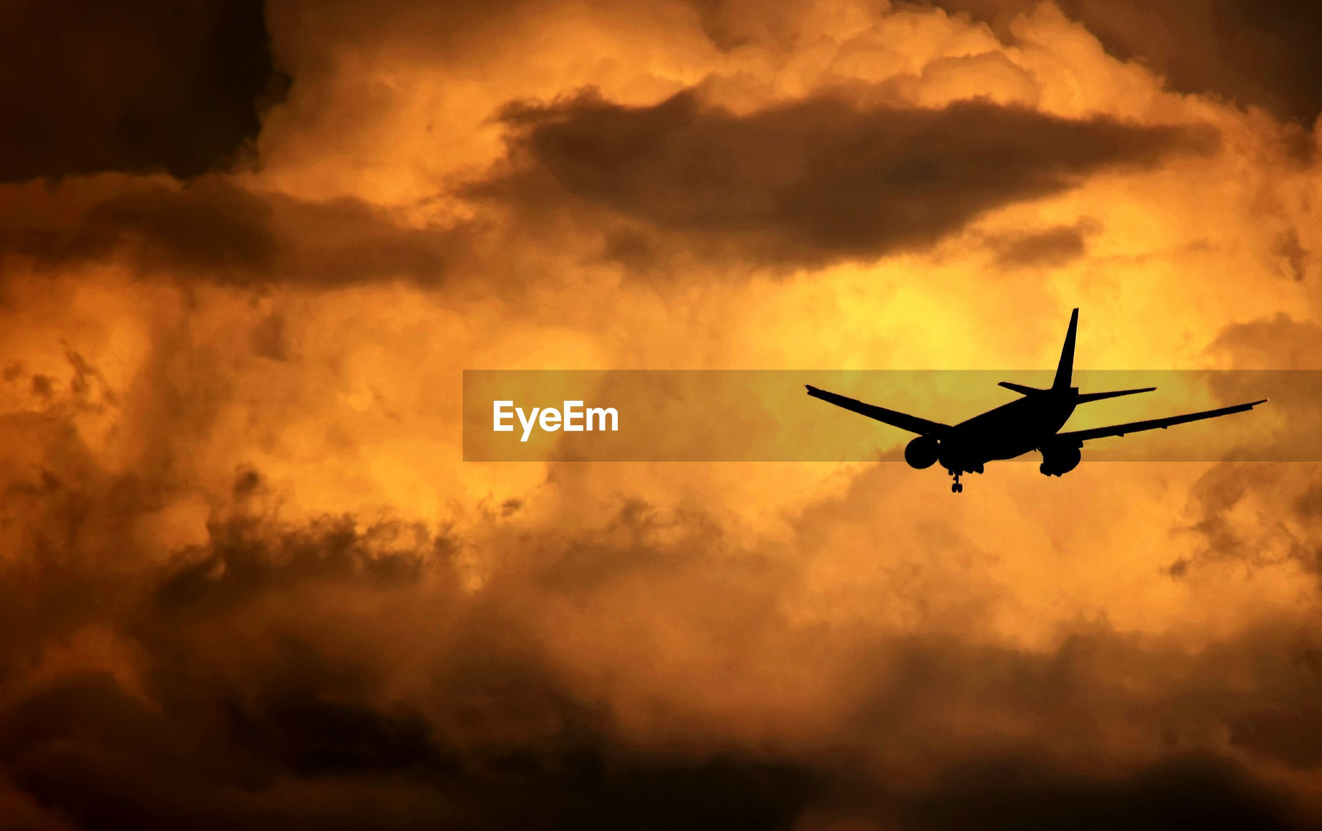 Low angle view of silhouette airplane flying against cloudy sky in stormy weather