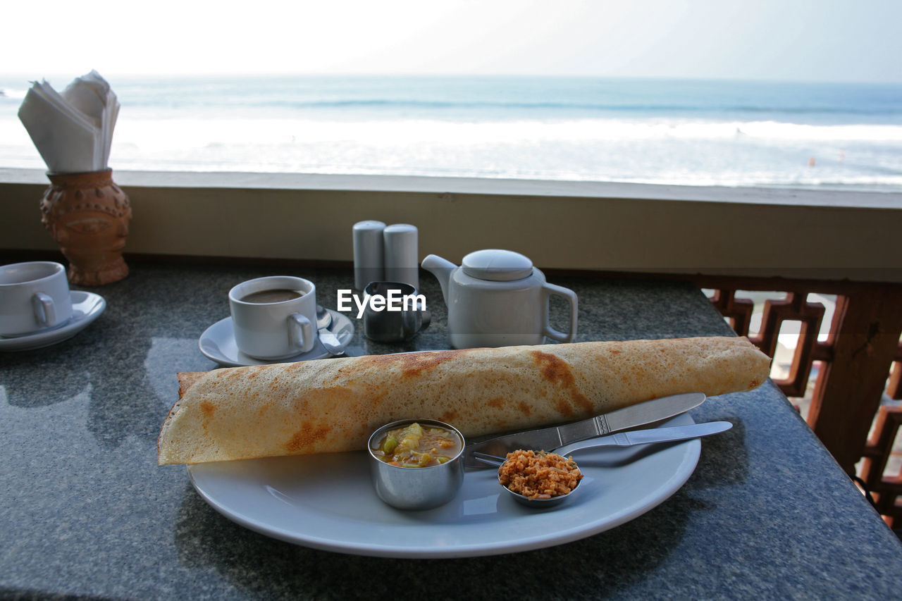 breakfast, food and drink, bread, table, plate, coffee cup, food, coffee - drink, sea, drink, water, healthy eating, day, real people, freshness, one person, outdoors, ready-to-eat, sky