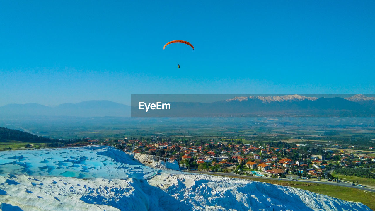 PEOPLE PARAGLIDING OVER LAND