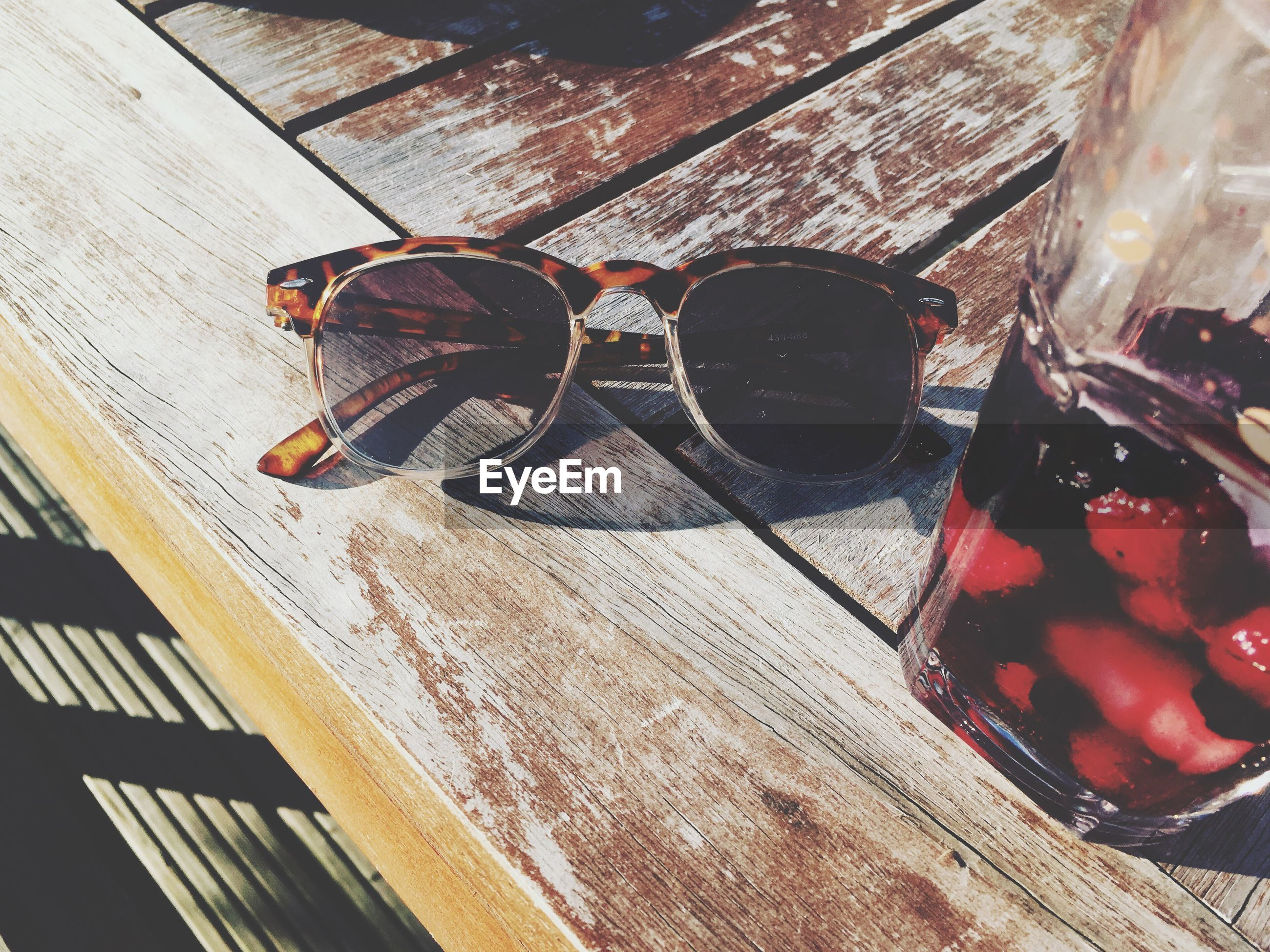 High angle view of sunglasses by drink on table