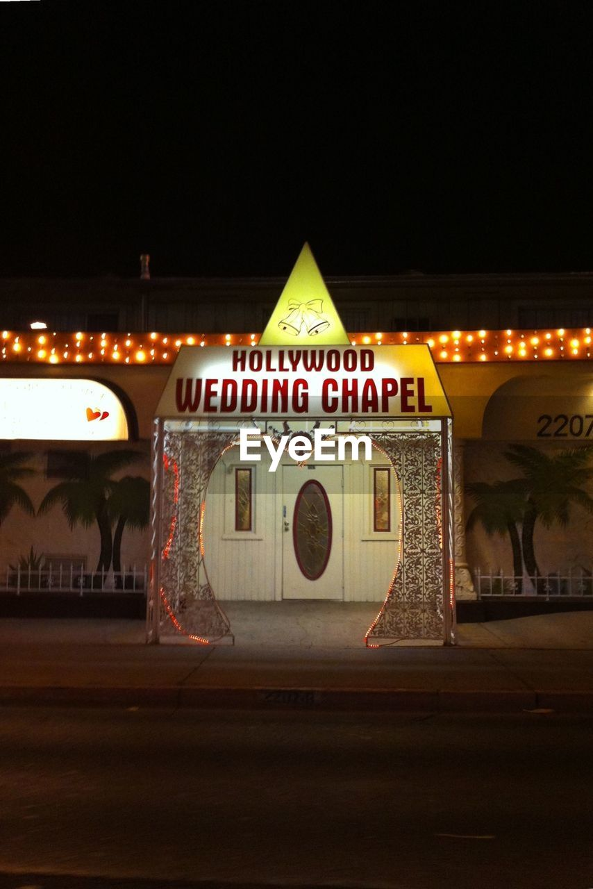 INFORMATION SIGN ON STREET AT NIGHT